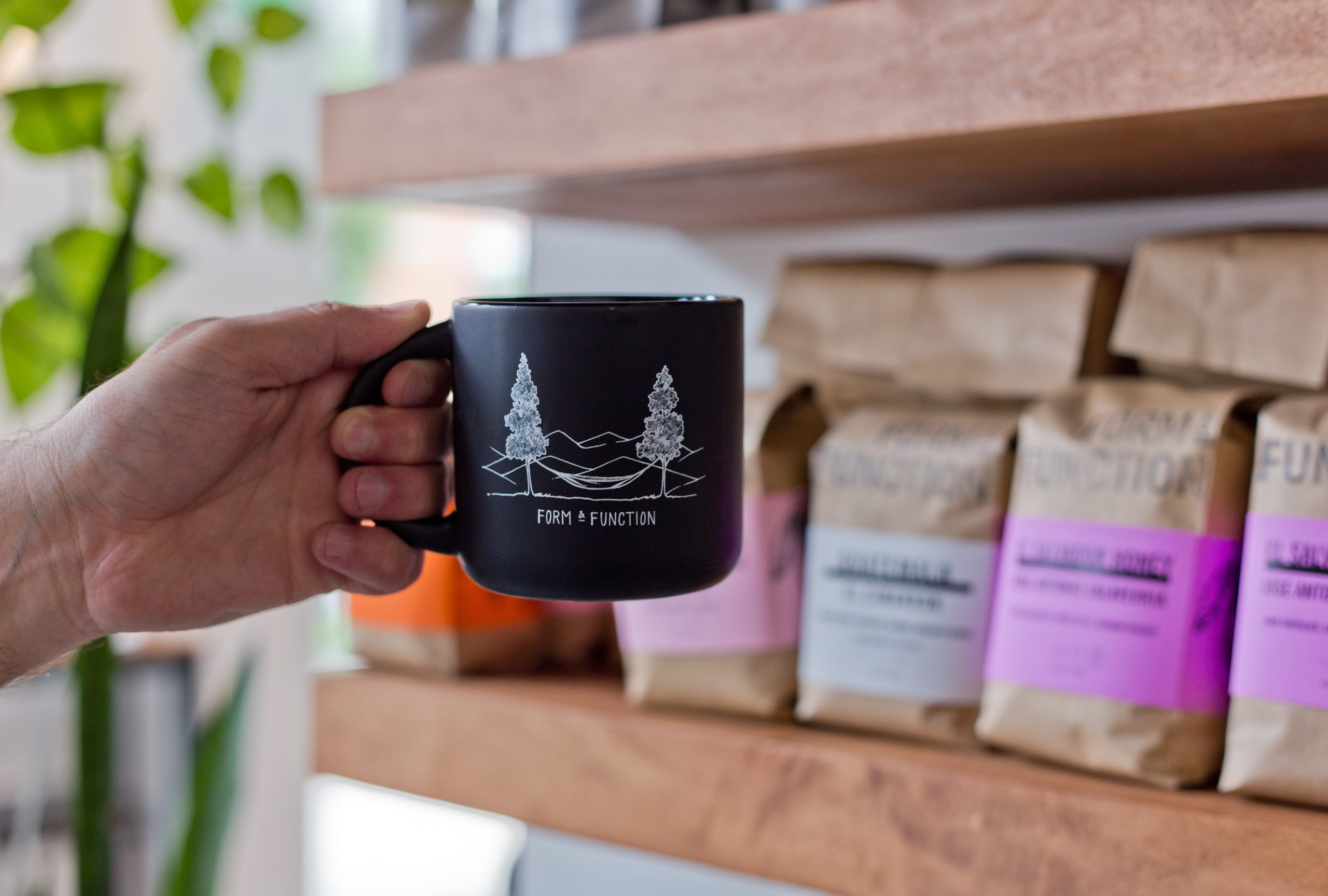 person holding a coffee mug against a backdrop of coffee beans