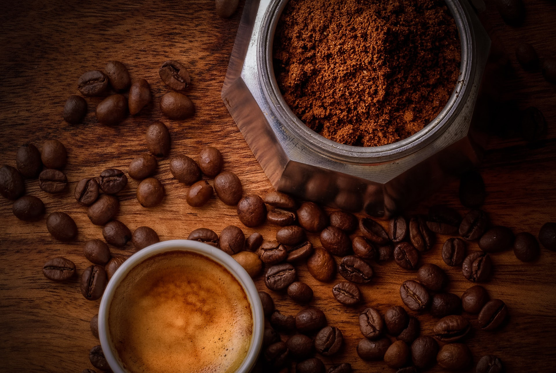 a cup of coffee, coffee beans, and coffee ground placed on a wooden table