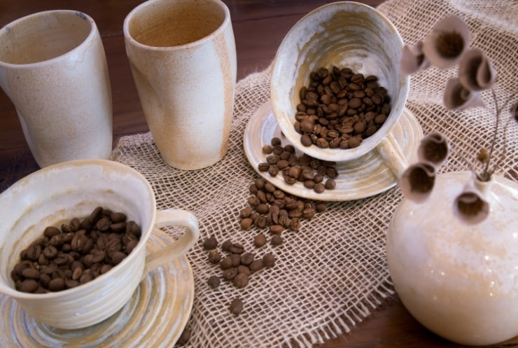 coffee beans spilling out from a ceramic cup
