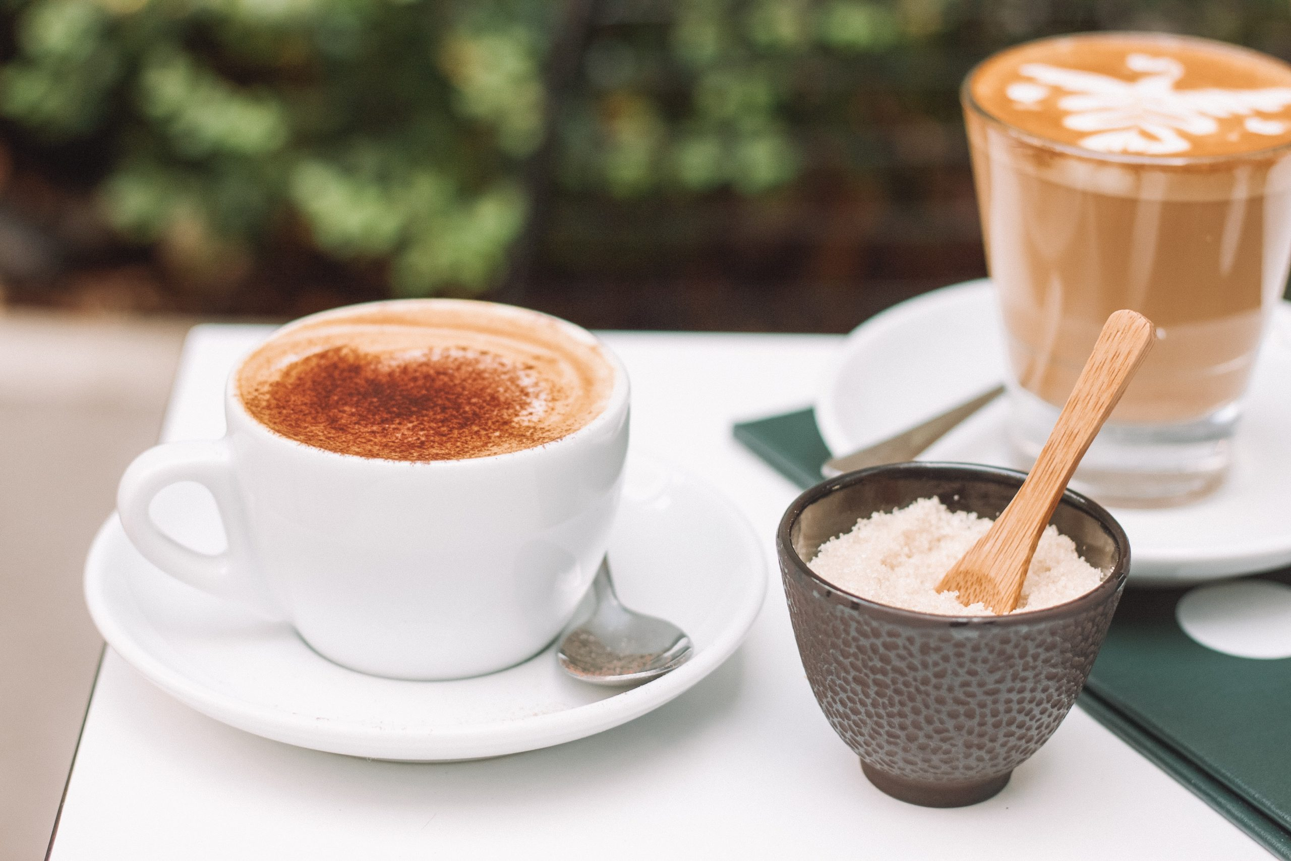 a bowl of sugar placed next to a cup of coffee