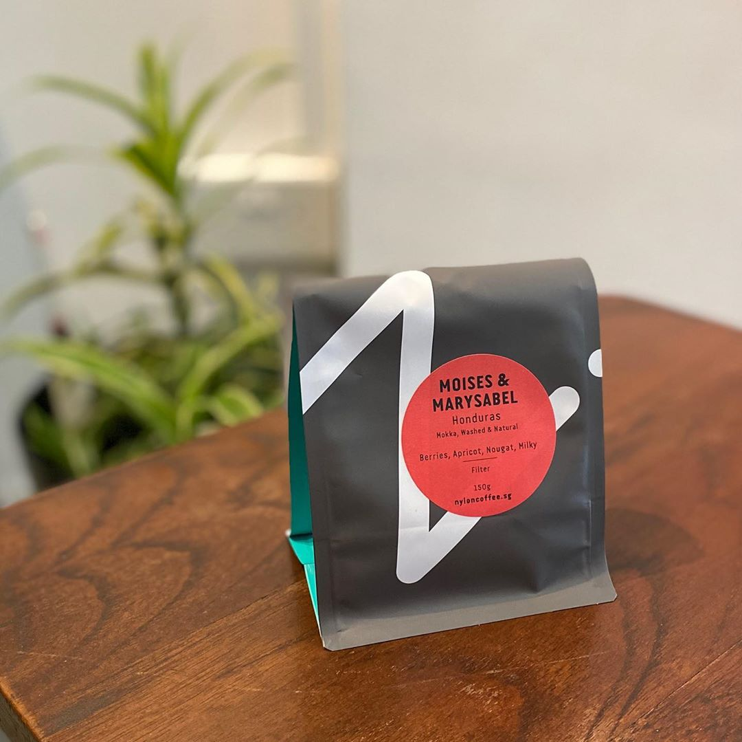 A bag of coffee beans from Nylon Coffee Roasters placed on a wooden table