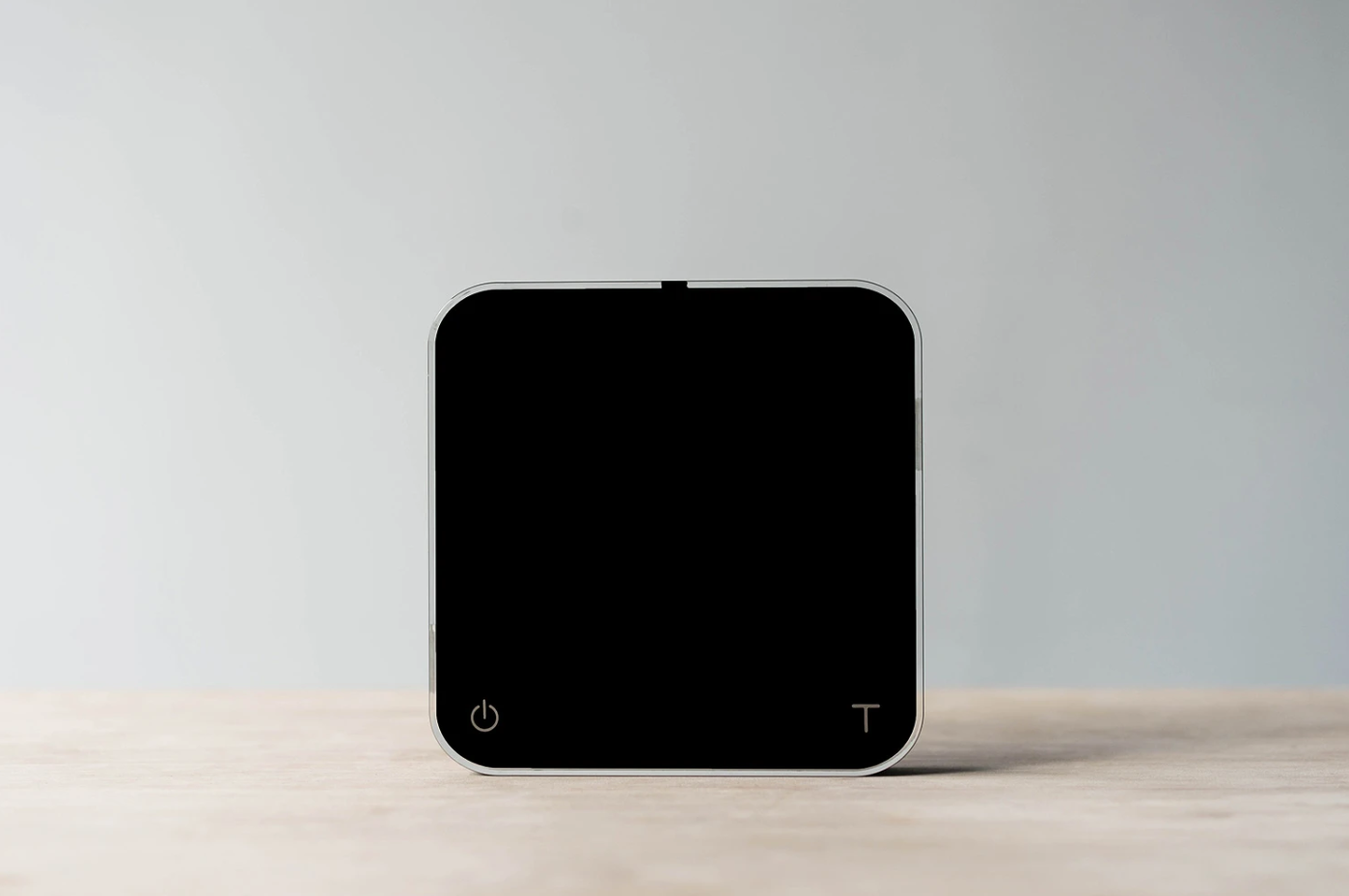 a black coffee weighing scale placed upright on a table