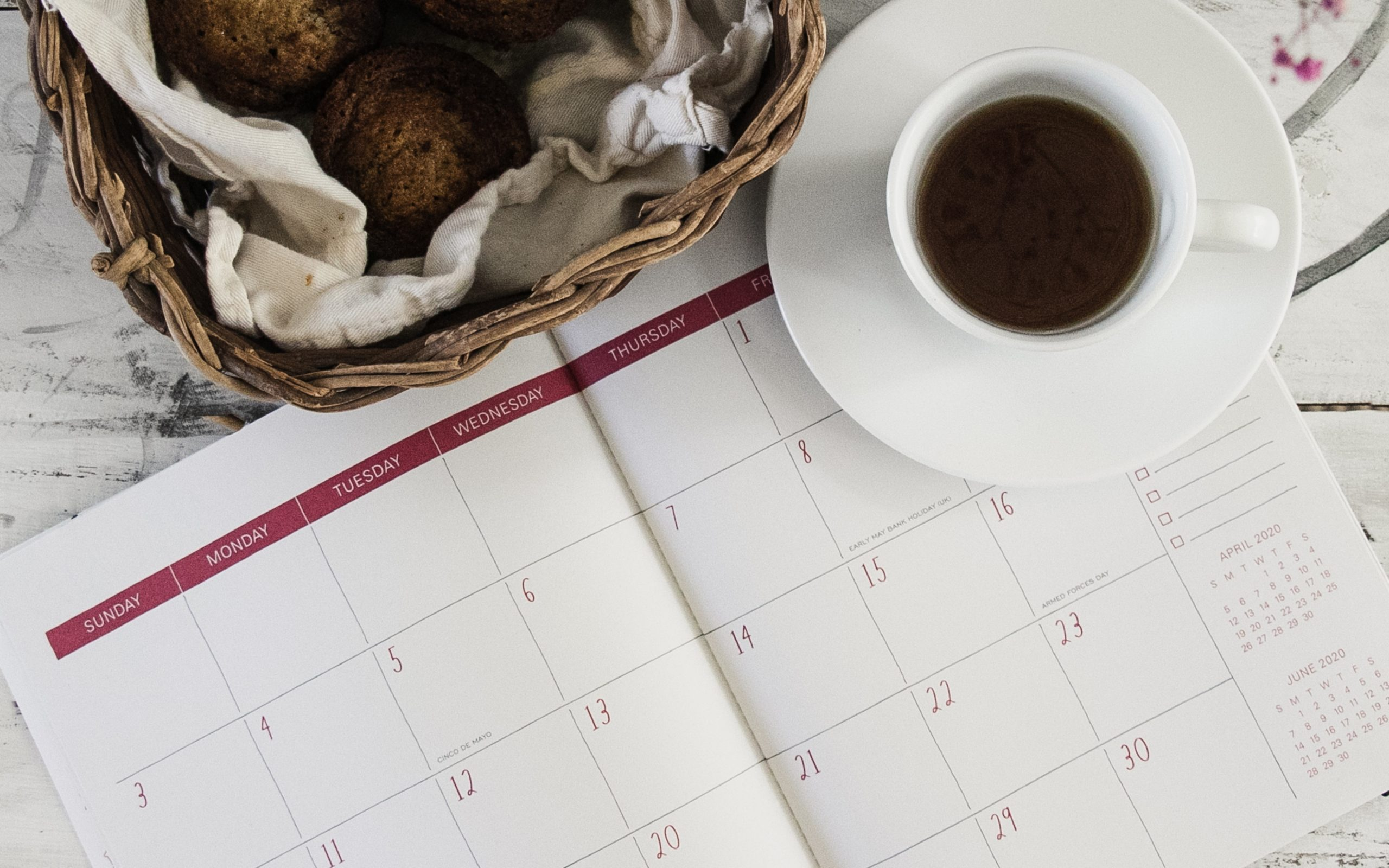 a cup of black coffee placed atop a calendar