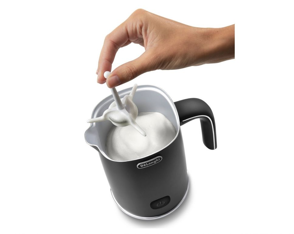 hand removing milk frothing wand from electric milk frother