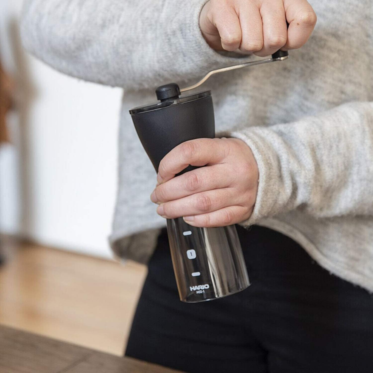 a lady manually grinding coffee beans in a coffee grinder