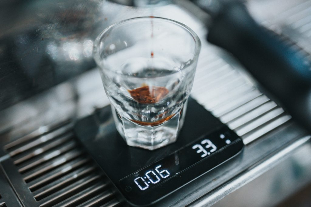 espresso dripping into a transparent glass cup that is sitting on a weighing scale