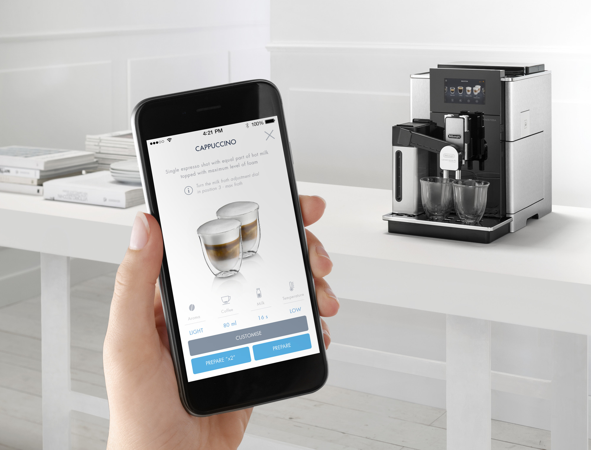 A person holding up a mobile phone with the De'Longhi Maestosa Coffee Machine in the background
