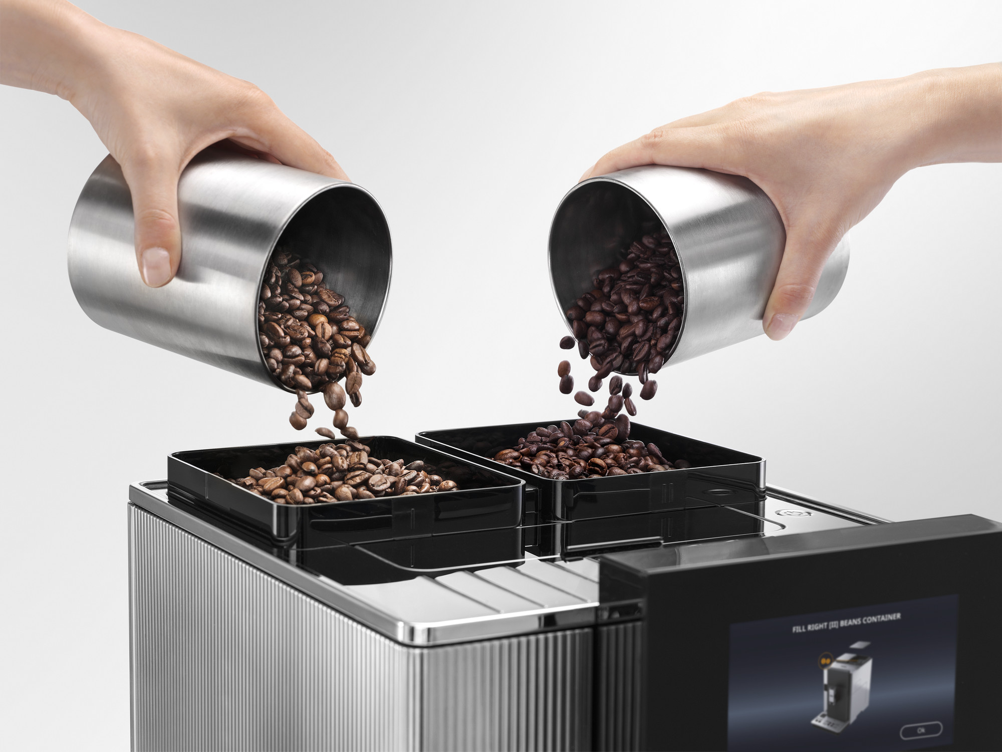 Pouring coffee beans into two separate bean hoppers of the De'Longhi Maestosa Coffee Machine