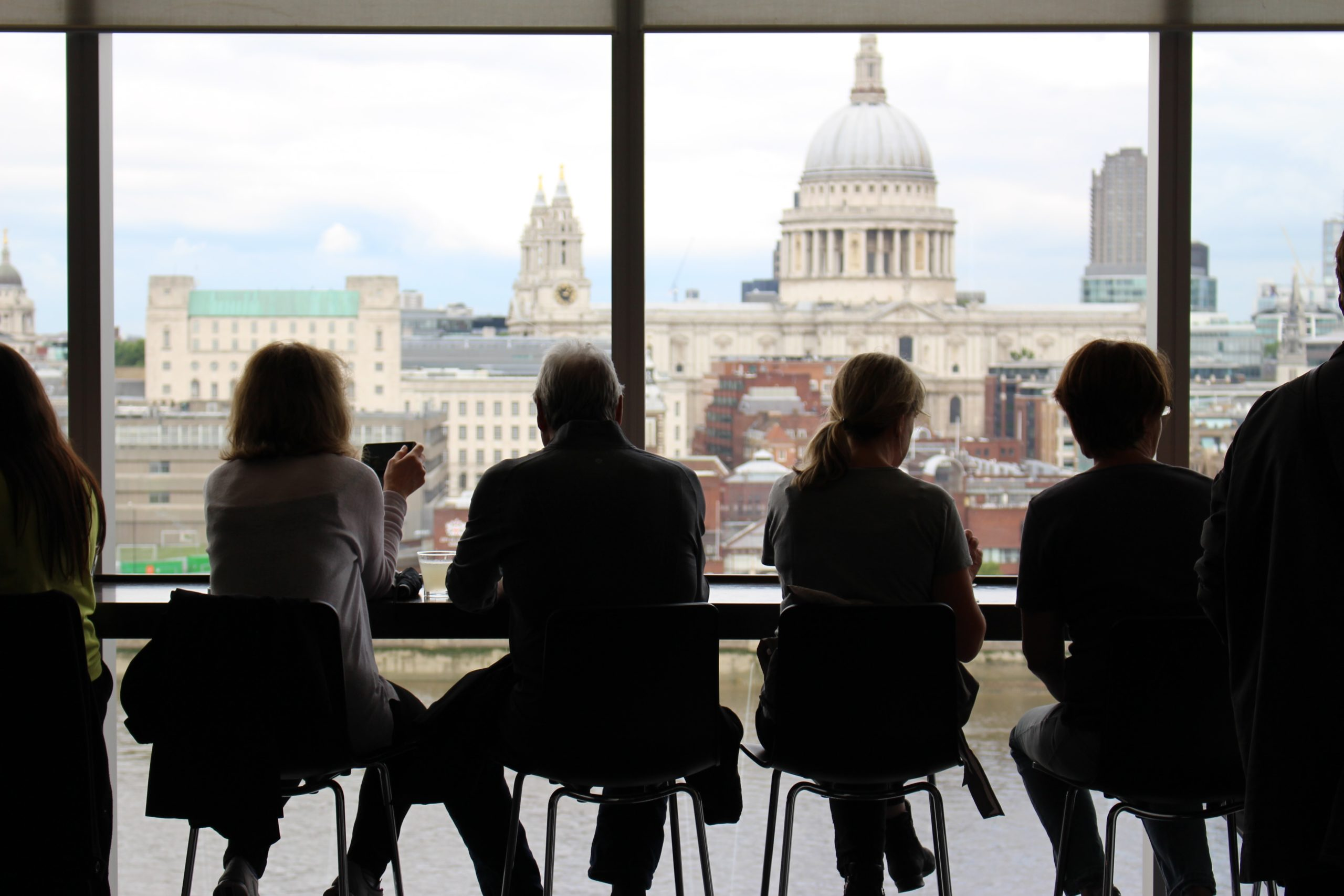 a back shot of people sitting along the window in a cafe in London