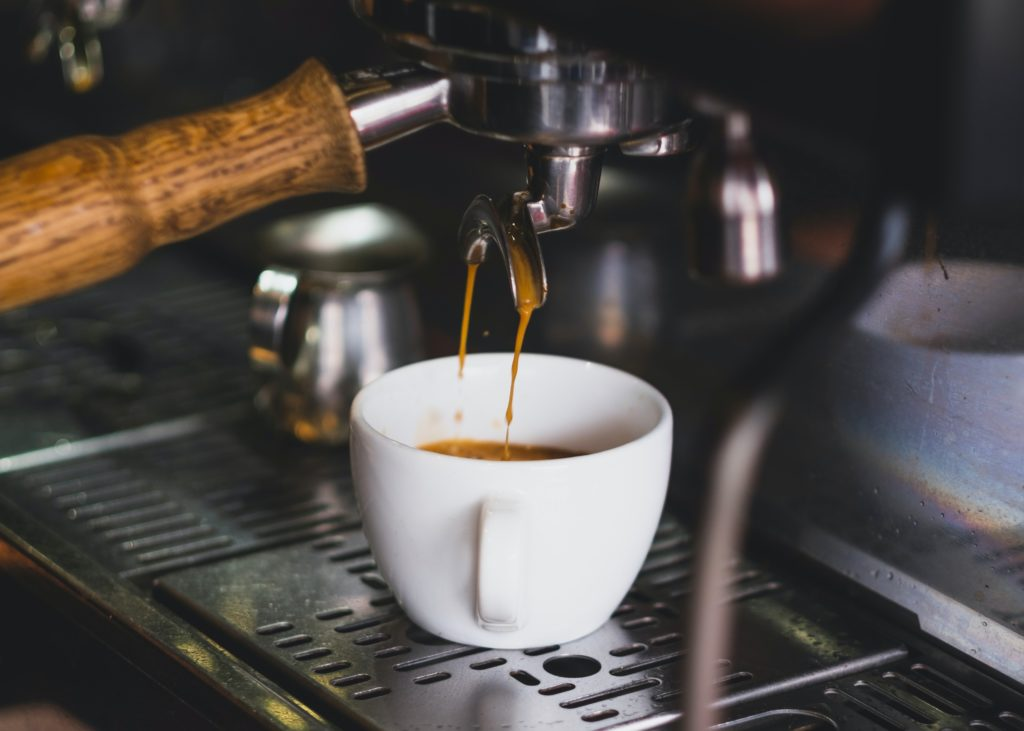 coffee being extracted from a coffee machine to a white cup