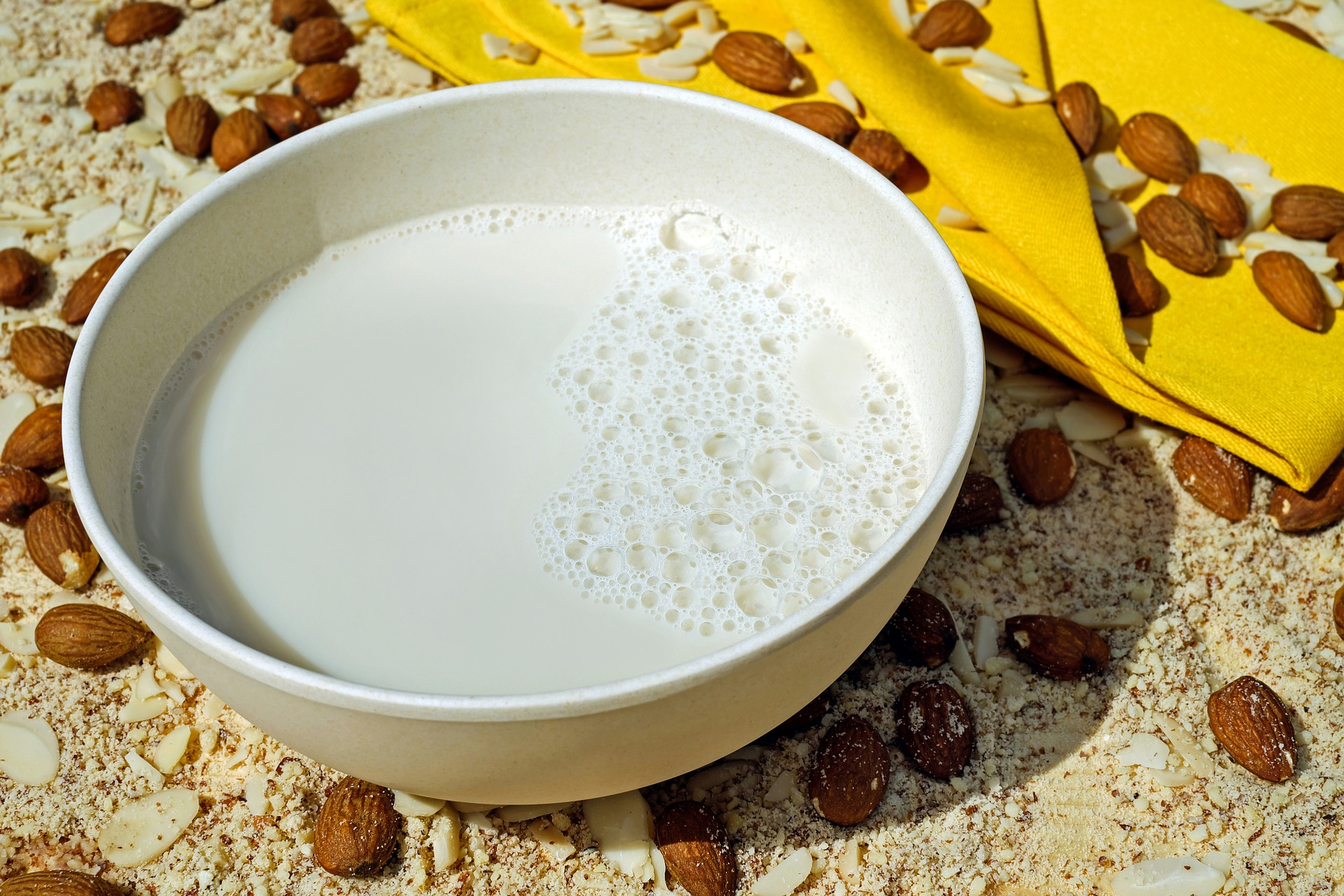a bowl of almond milk with almonds scattered around the bowl
