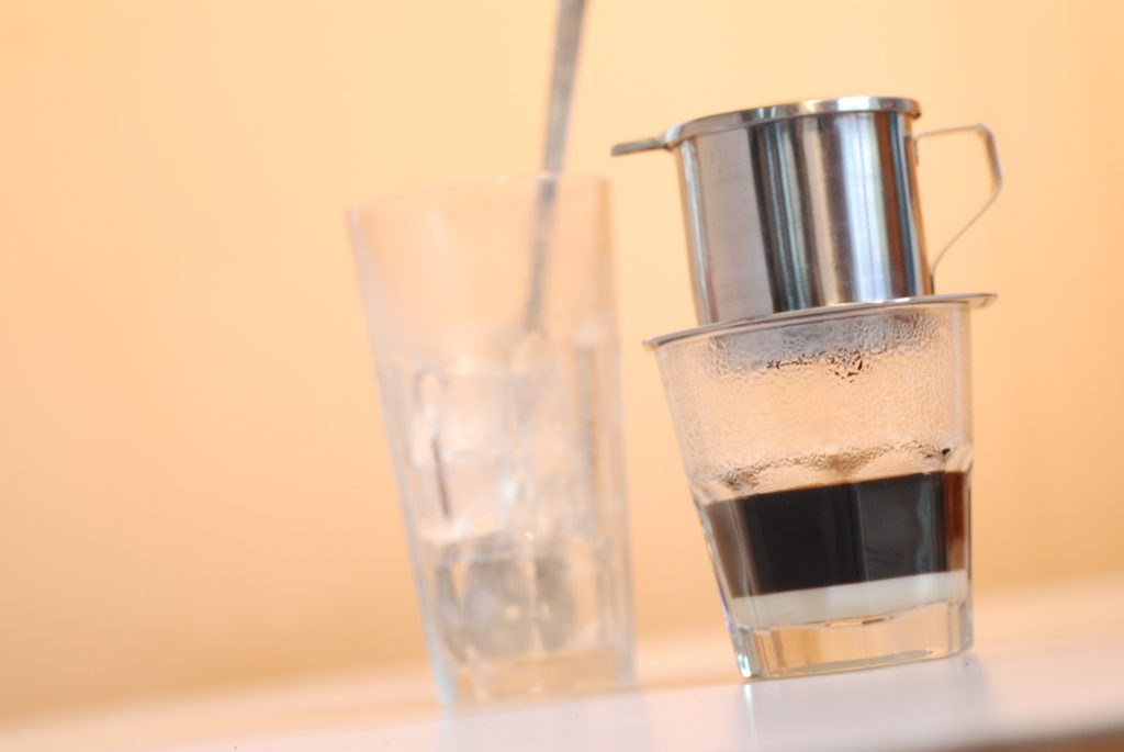 Vietnamese drip coffee and an empty tall glass on a table