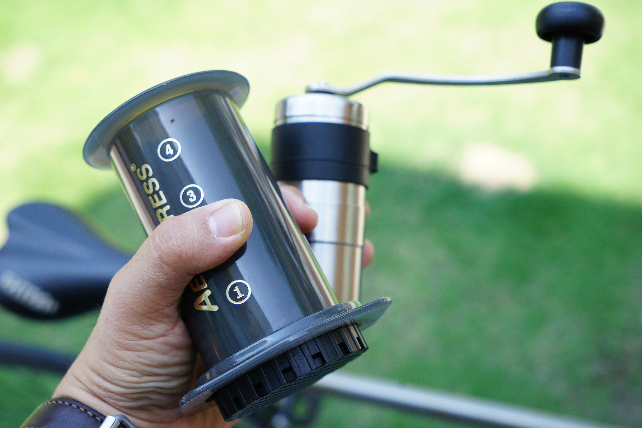 an aeropress and portable coffee grinder held in a hand