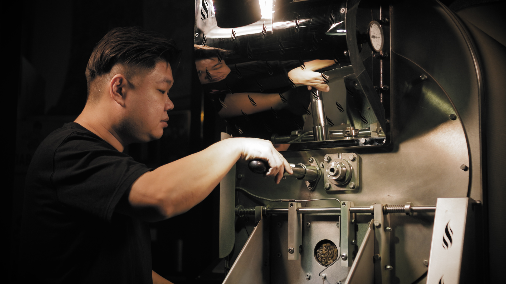 a coffee roaster removing coffee beans from a coffee roasting machine