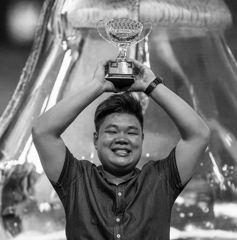 a man holding up a trophy above his head