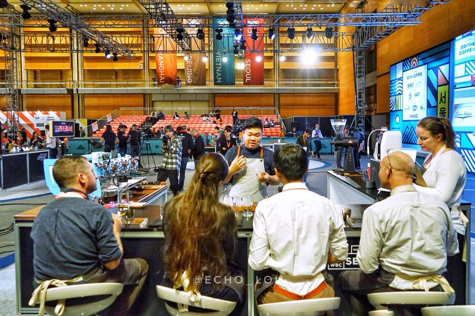 a barista pouring coffee for four judges at the world barista championship