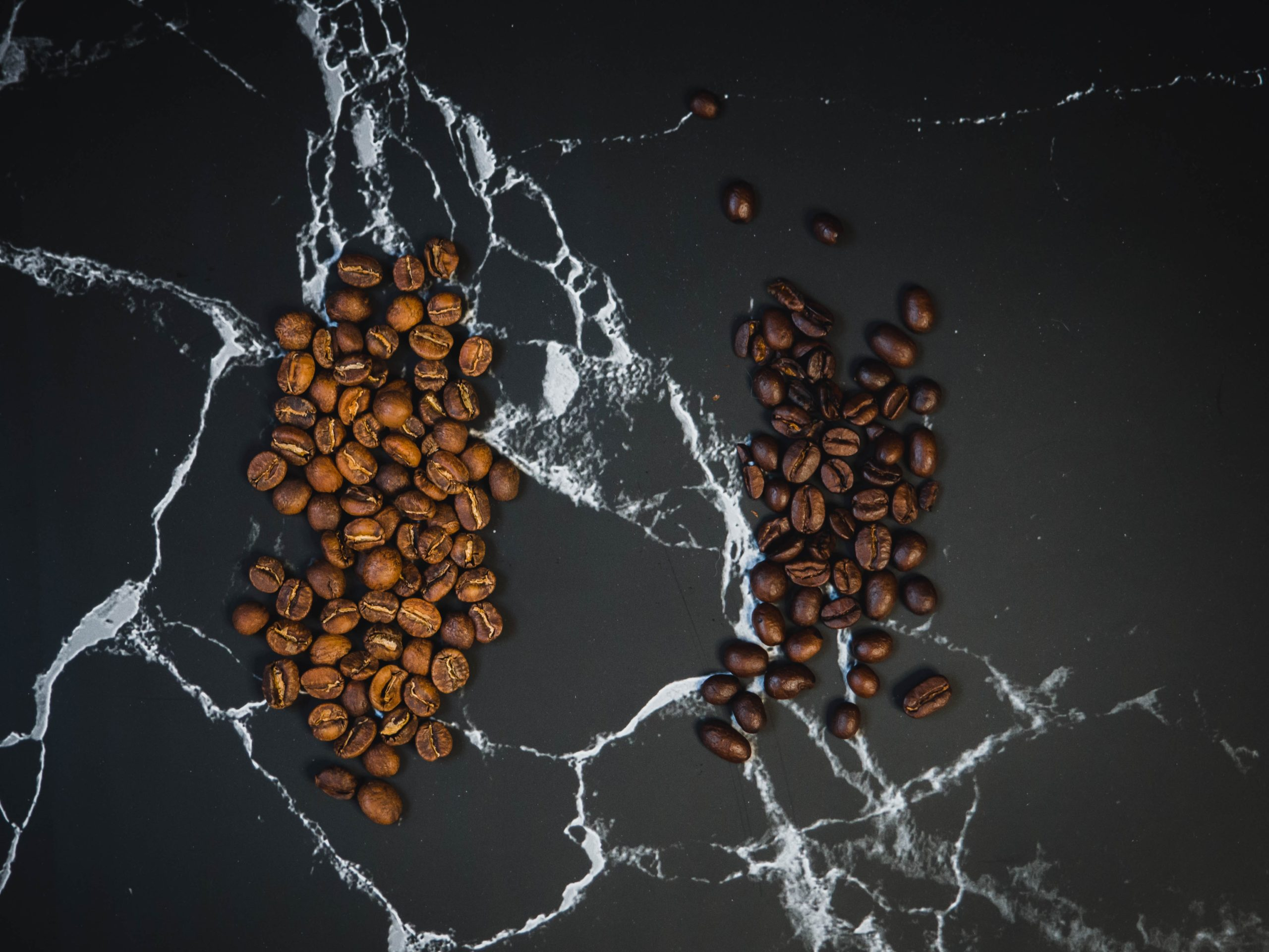 light and dark roast coffee beans placed on a marble table