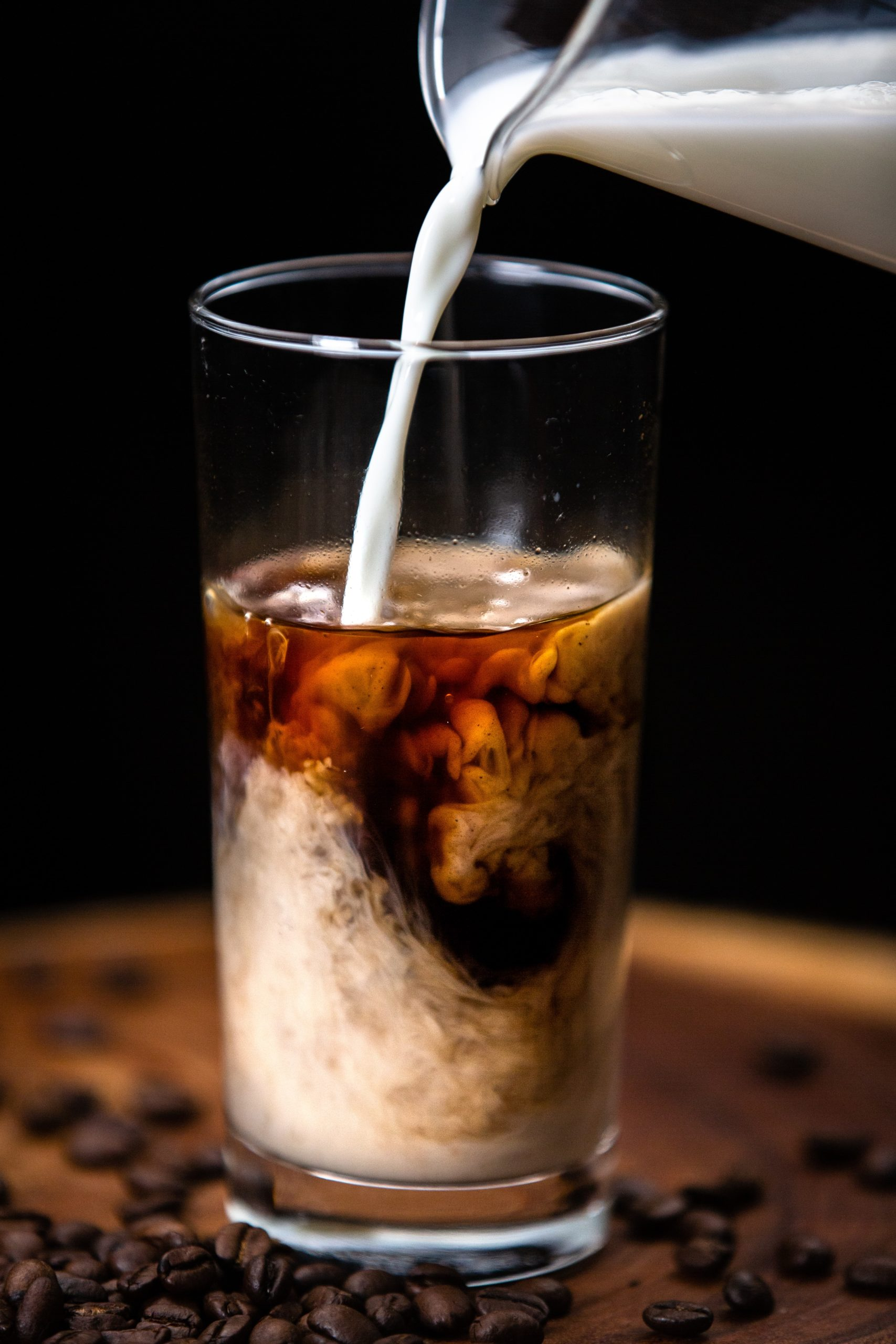 milk being pouring into a glass of cold brew
