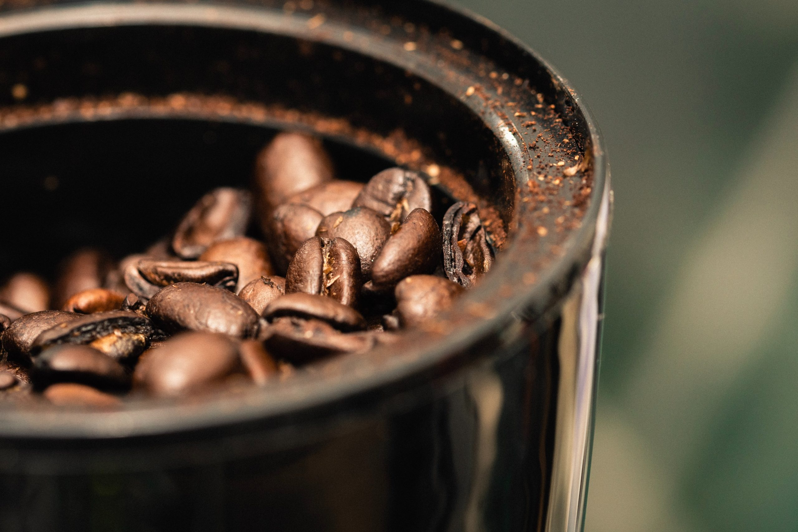 a close up shot of coffee beans in a coffee grinder