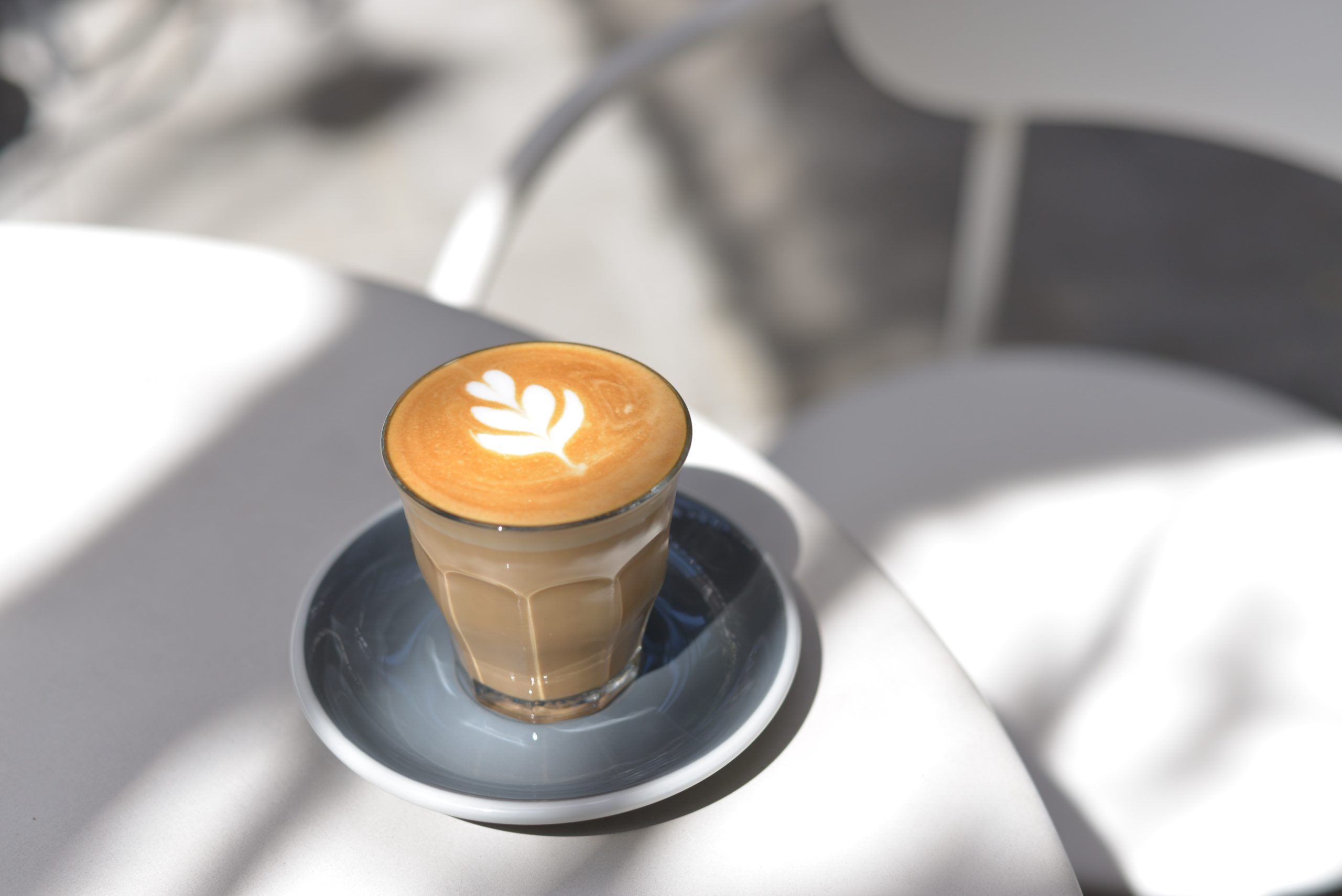a cup of latte art placed on a marble table