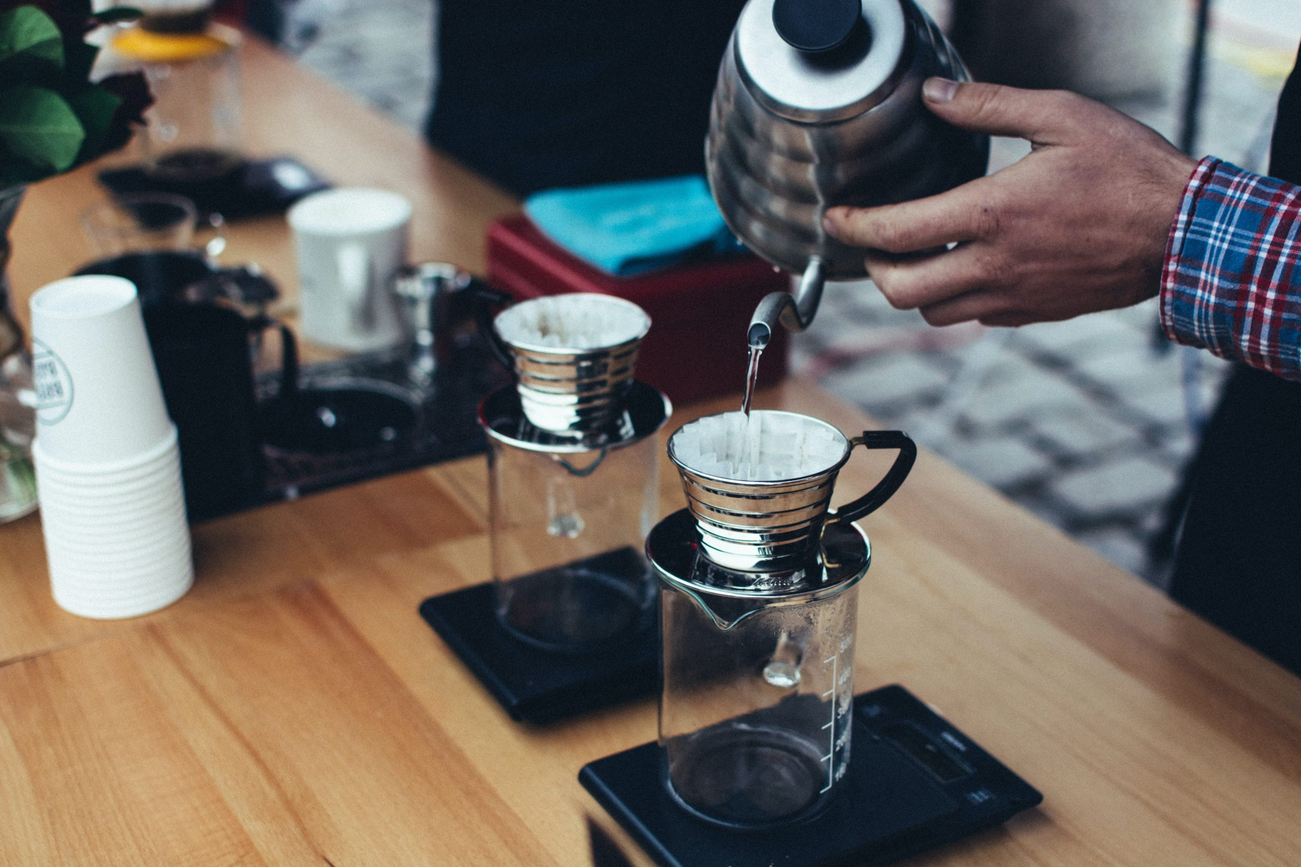 a person pouring water over a filter drip coffee