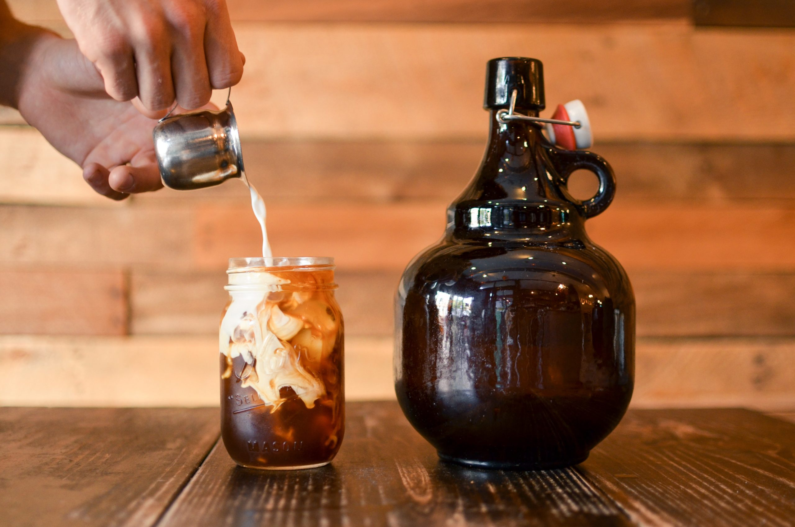 a person pouring milk into a glass of cold brew