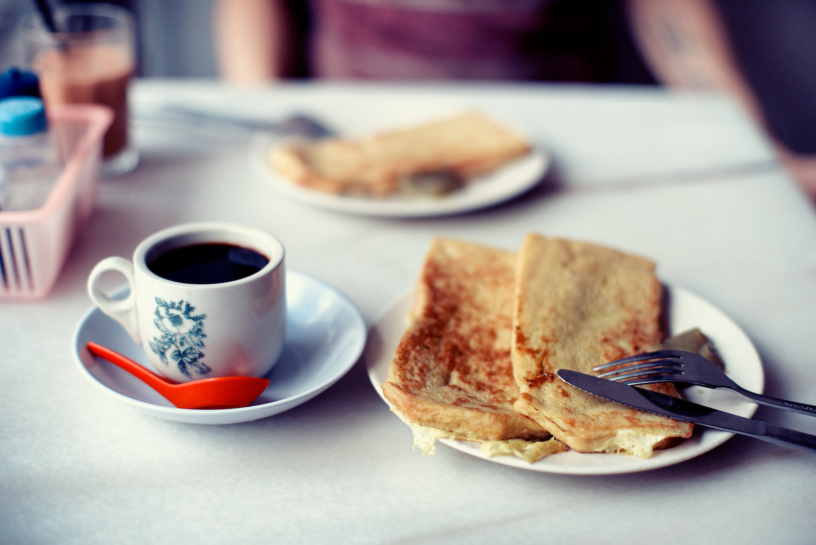 a cup of coffee served with a plate of french toast