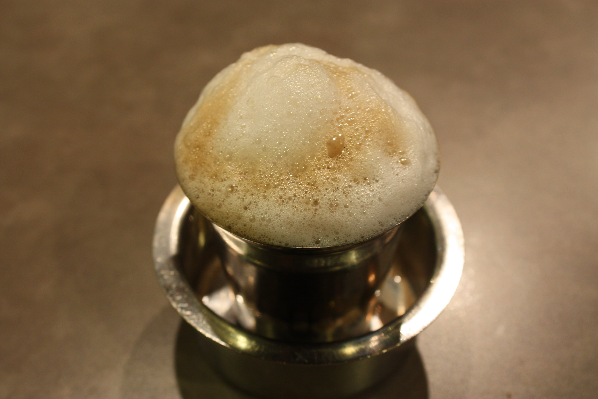 a cup of Southern India filter coffee topped with milk foam