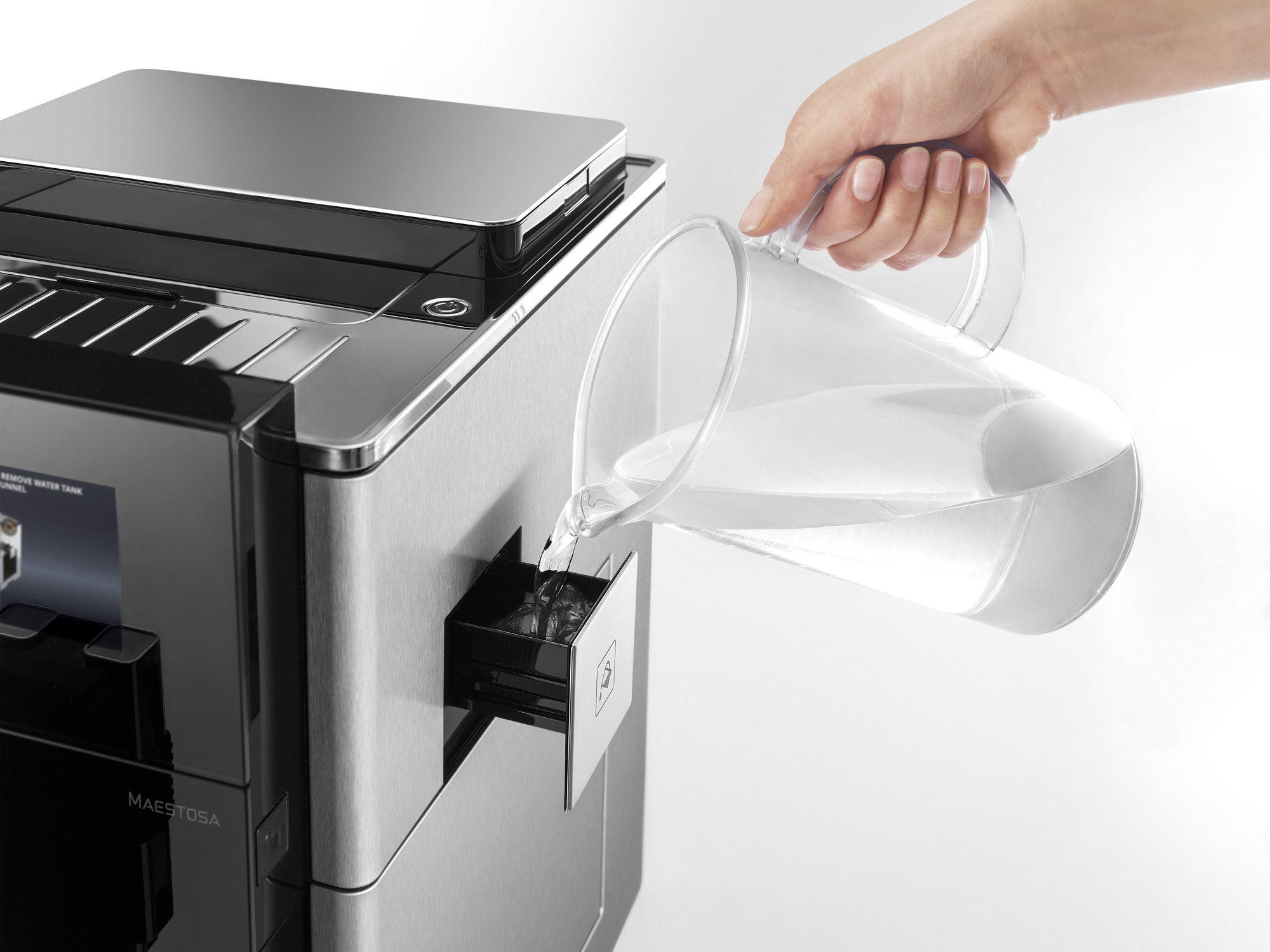 Pouring water into a coffee machine's water tank