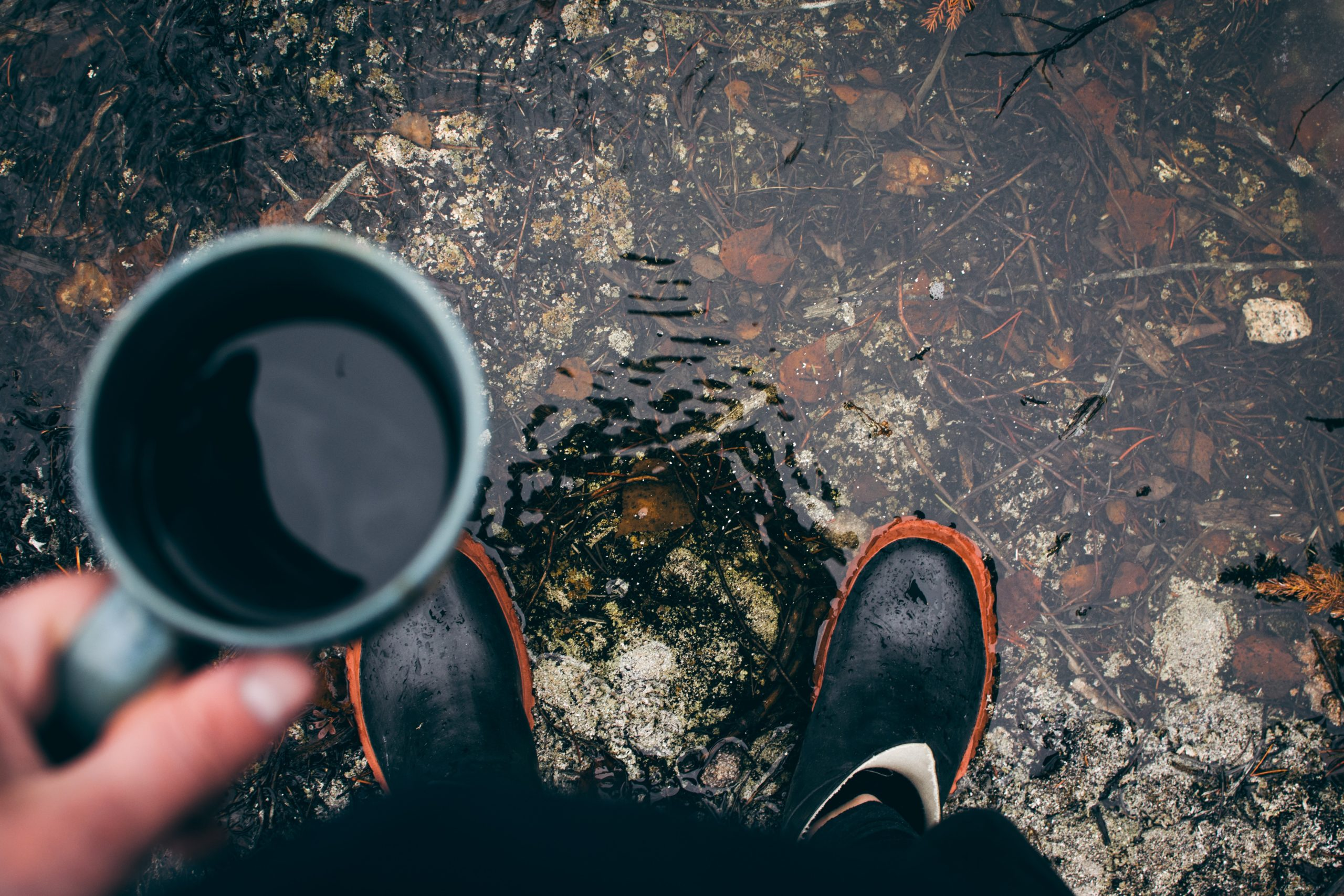 a man standing on a water puddle with a cup of coffee in his hand