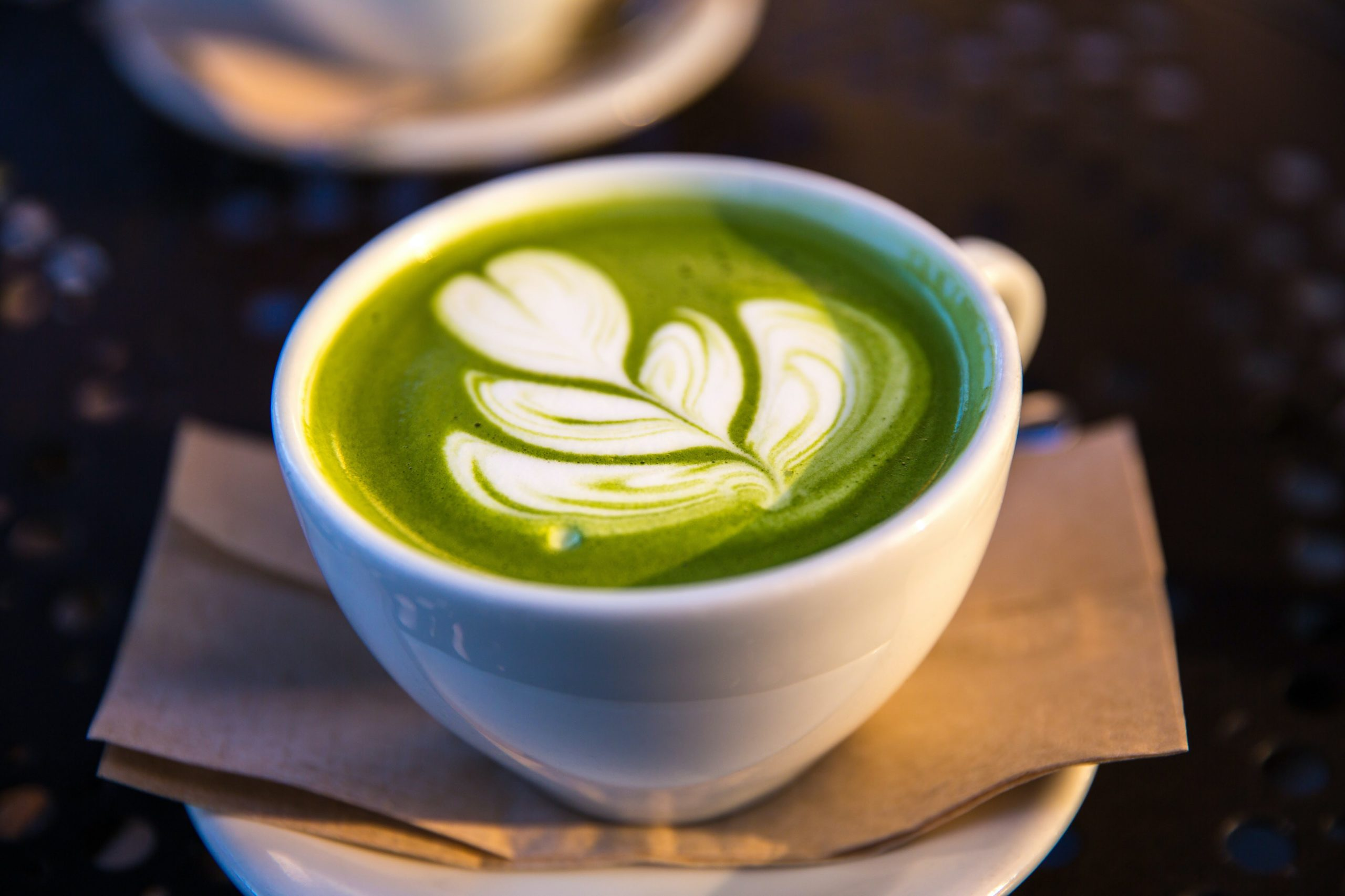 a cup of green tea latte with coffee art