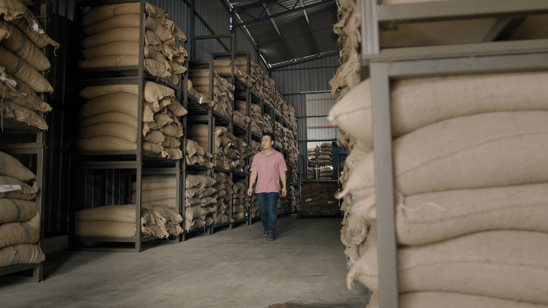 a man standing in the middle of a coffee storage warehouse