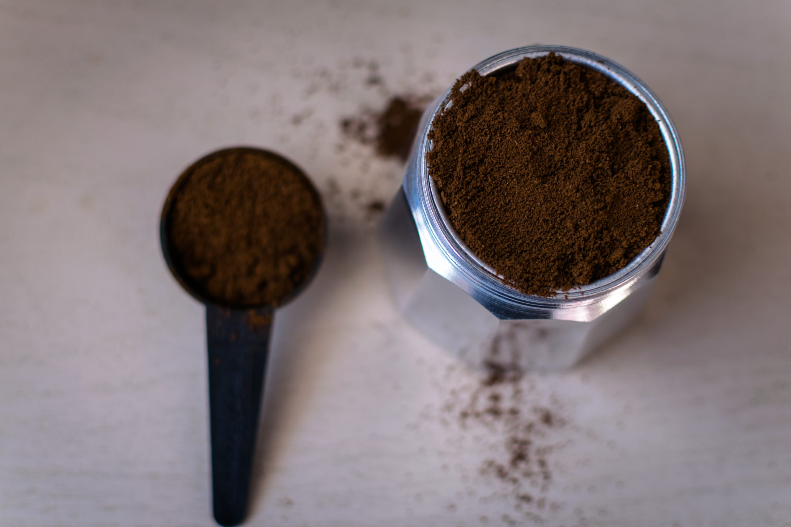 a scoop of coffee grounds and a jar of coffee grounds
