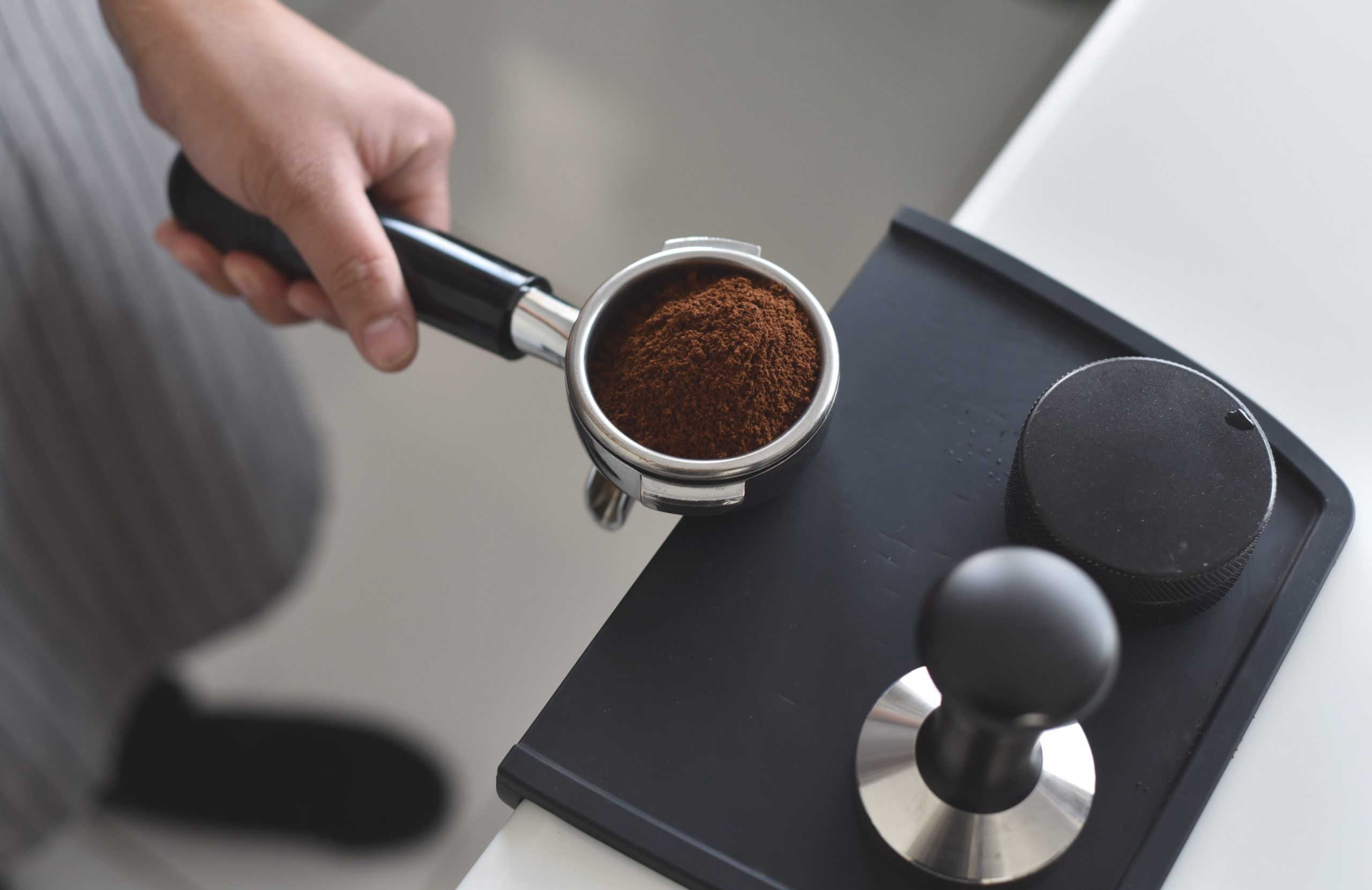 a person tamping coffee grounds