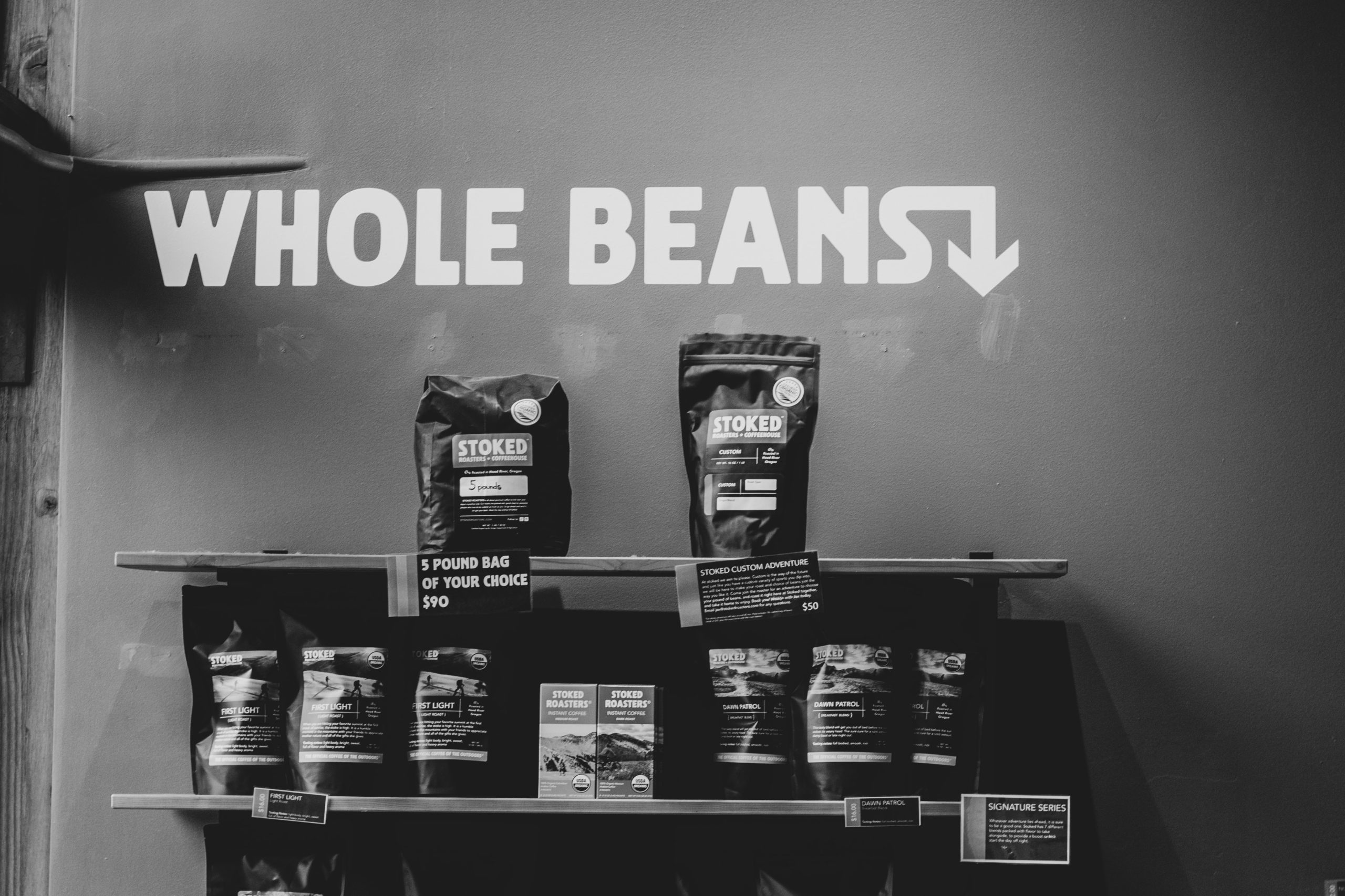 a black and white photo of bags of coffee beans on a shelf display