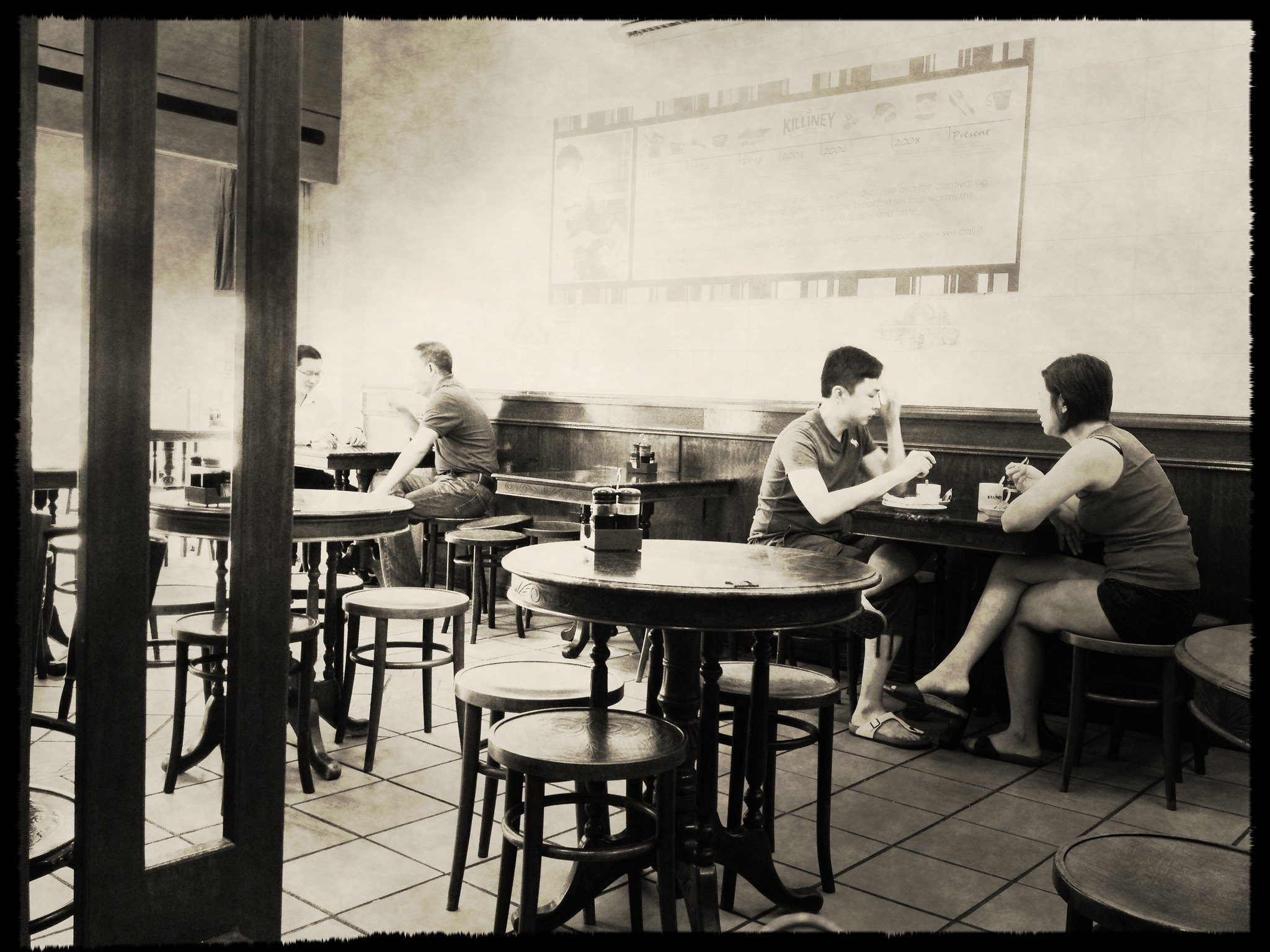 an old photo of people drinking coffee at a kopitiam