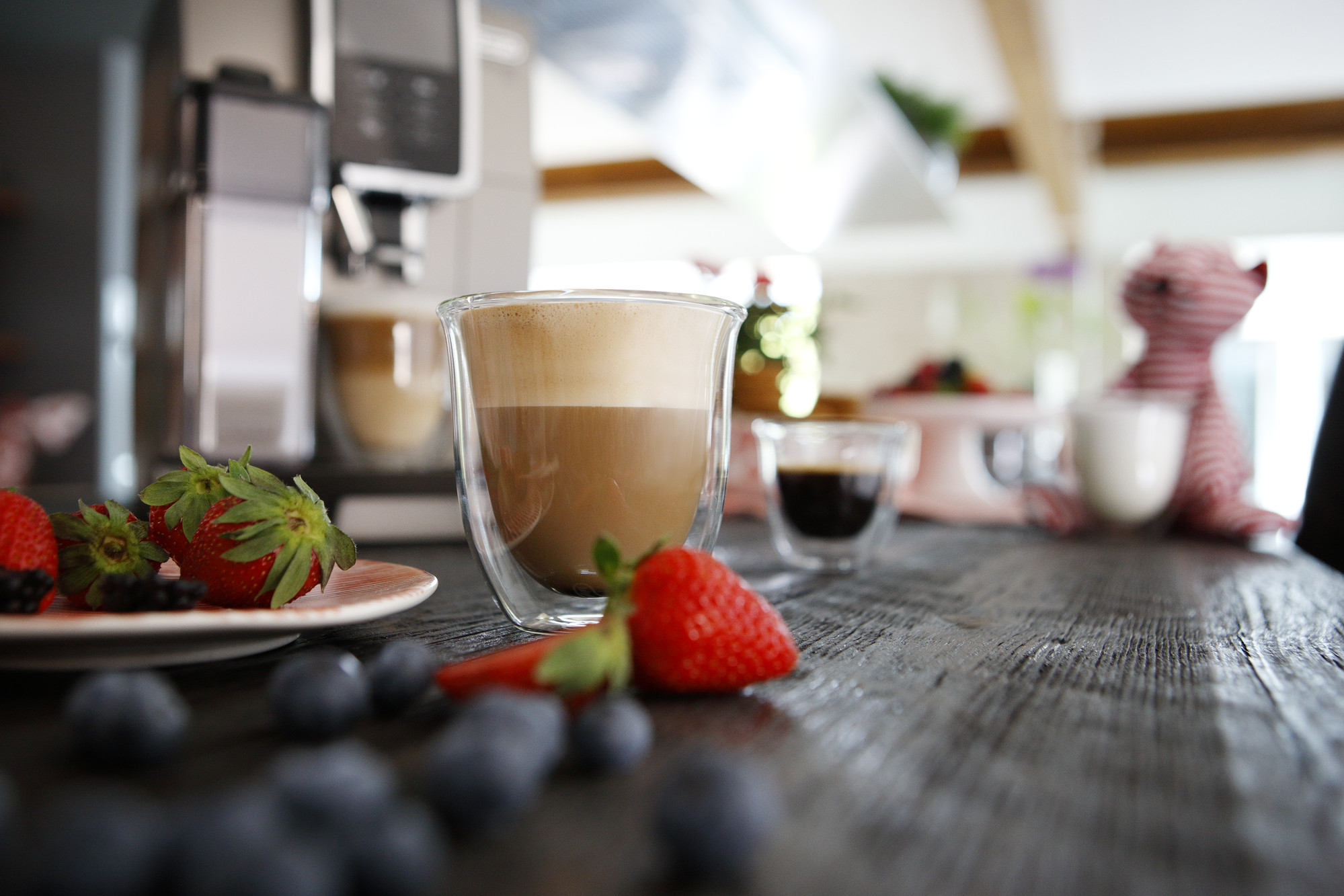 strawberries and blueberries placed around a cup of cappucino