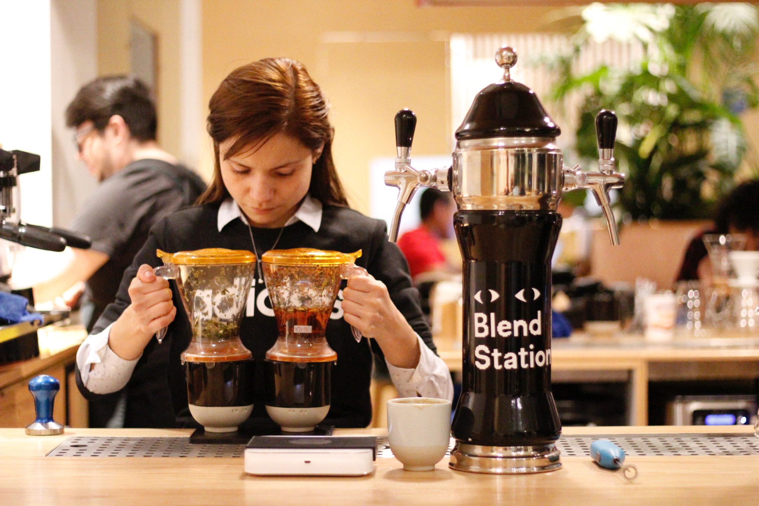 a barista holding two drip coffee