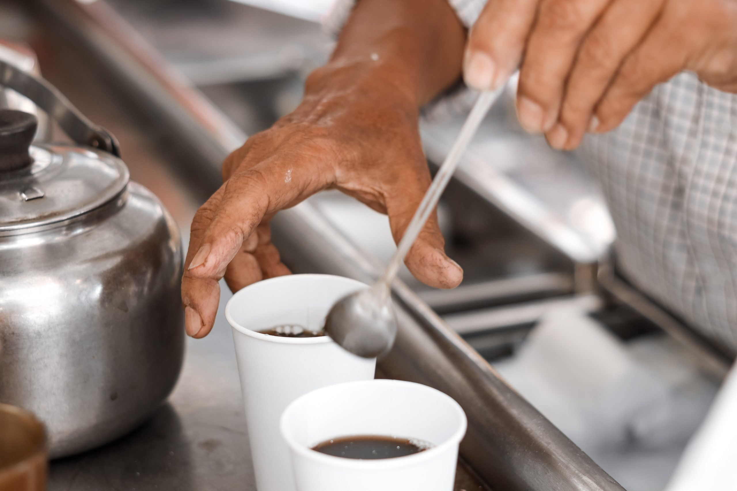 a man holding a spoon to stir a cup of coffee