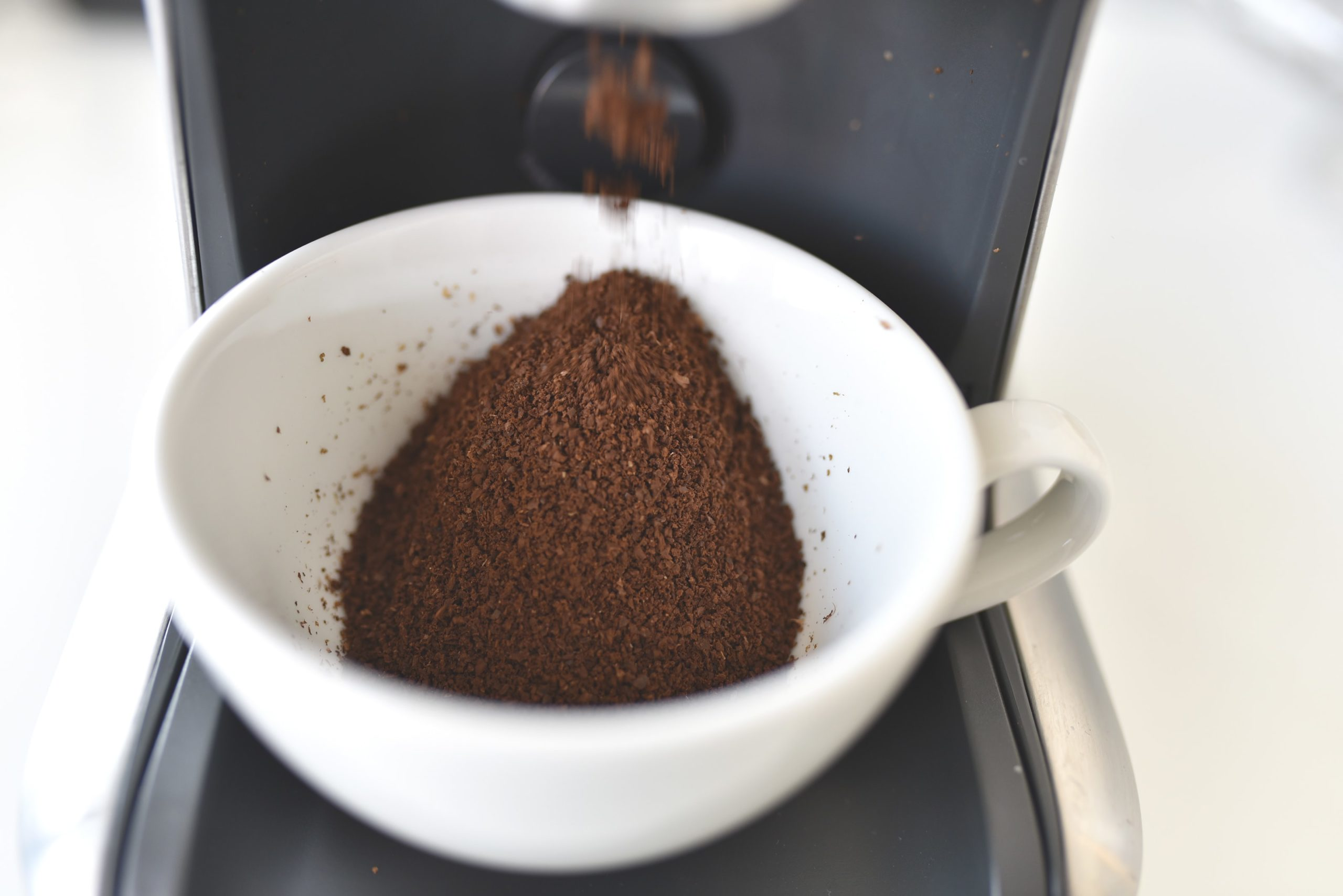 coffee being grounded into a white cup