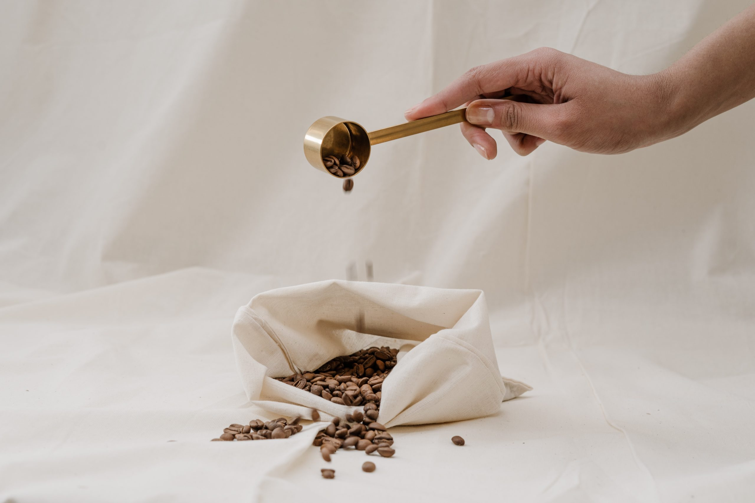 a person pouring a scoop of coffee beans into a bag