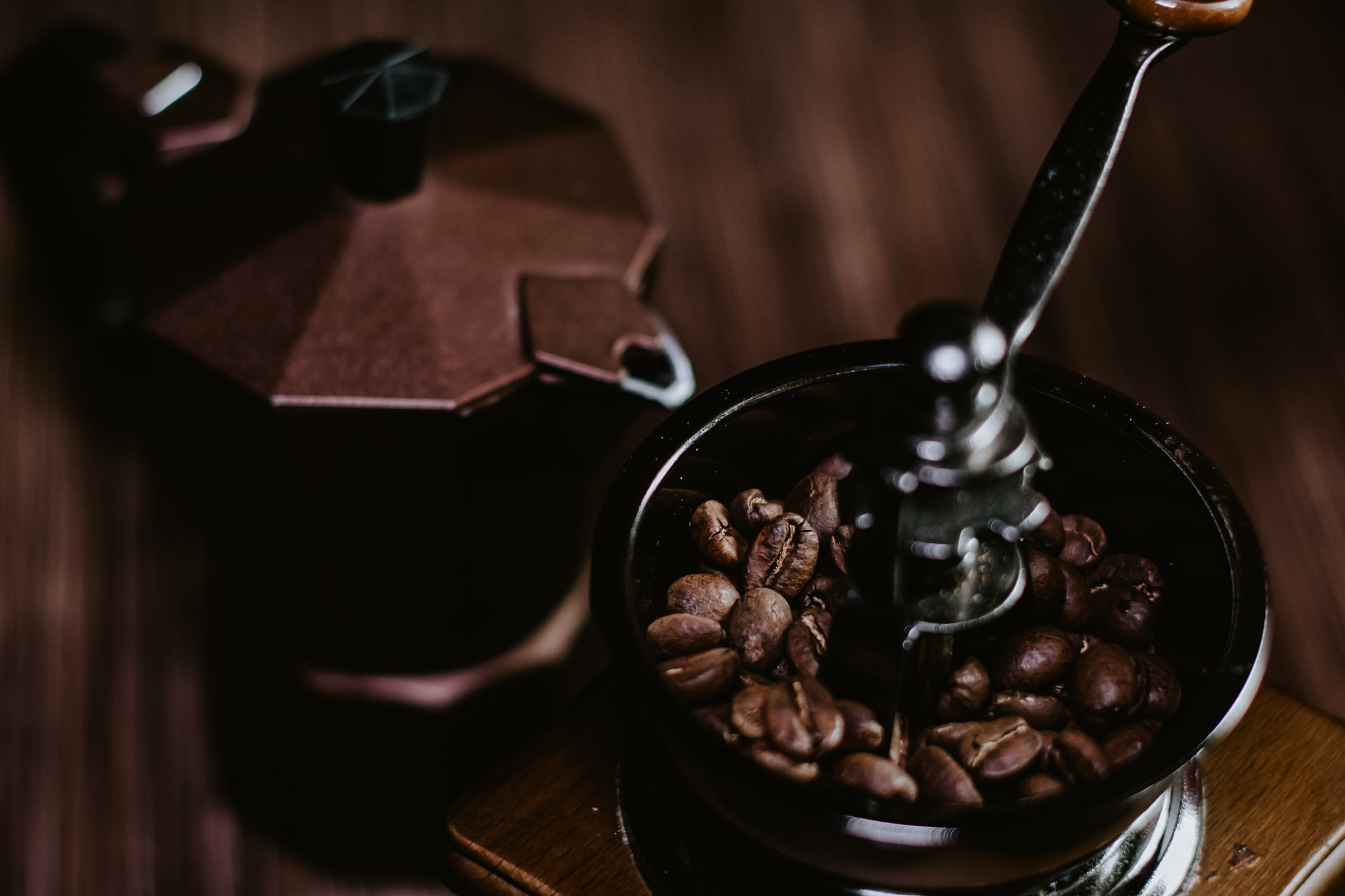 a moka pot placed next to a manual coffee bean grinder