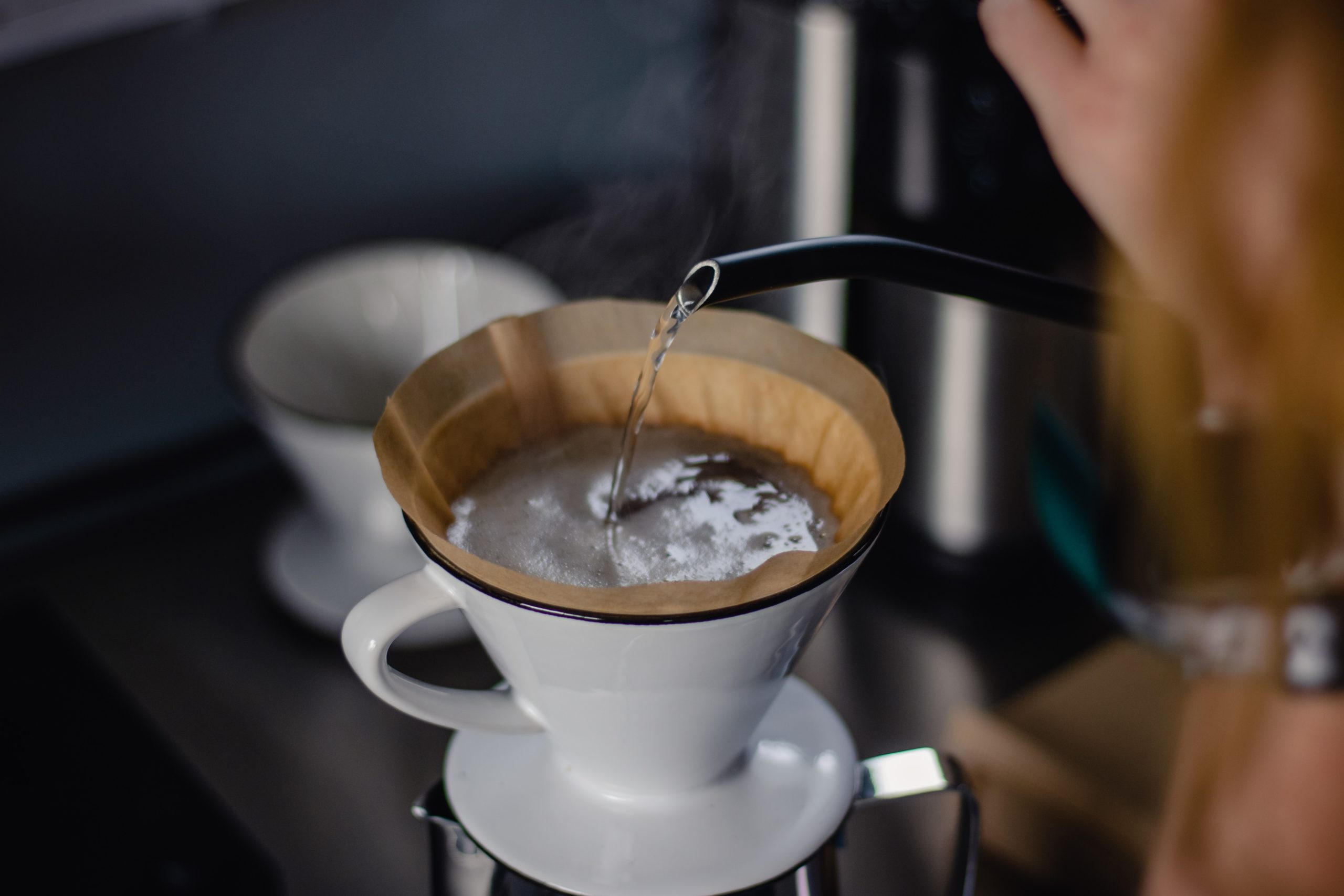 pouring hot water into a pour over from a gooseneck kettle