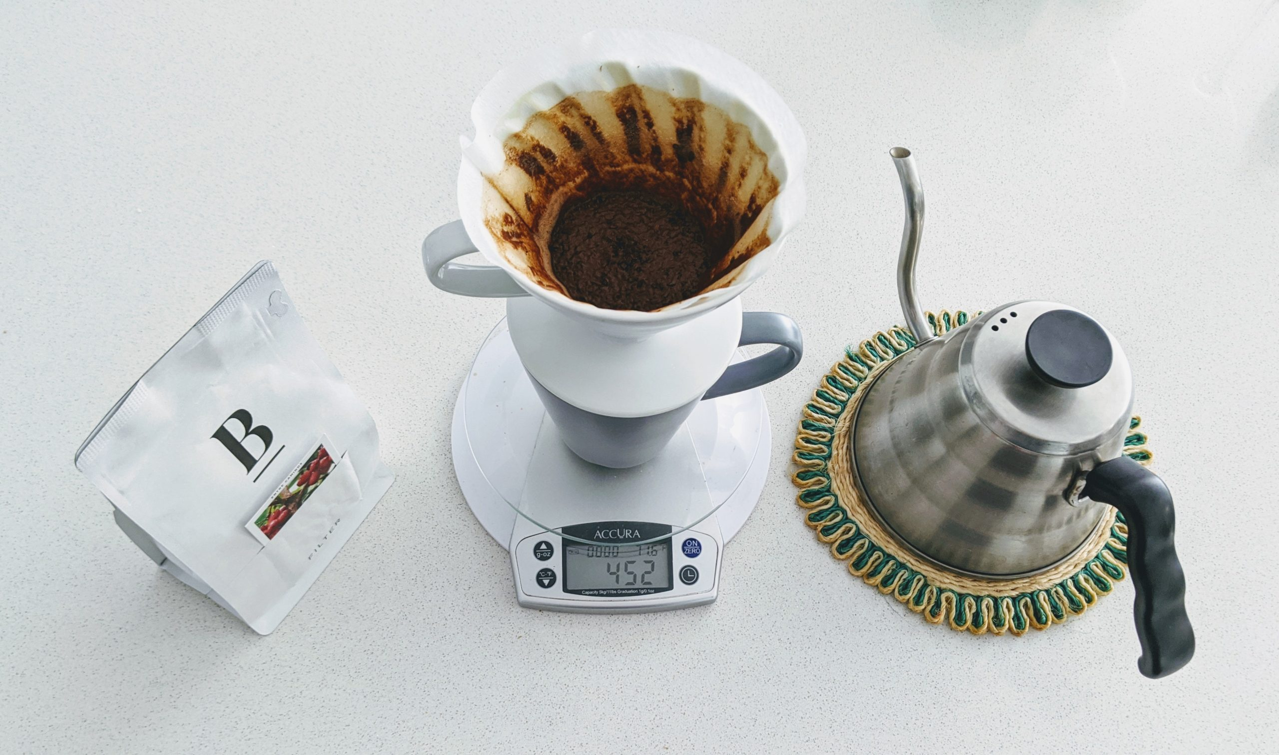 a bag of coffee beans, a pour over, and a gooseneck kettle