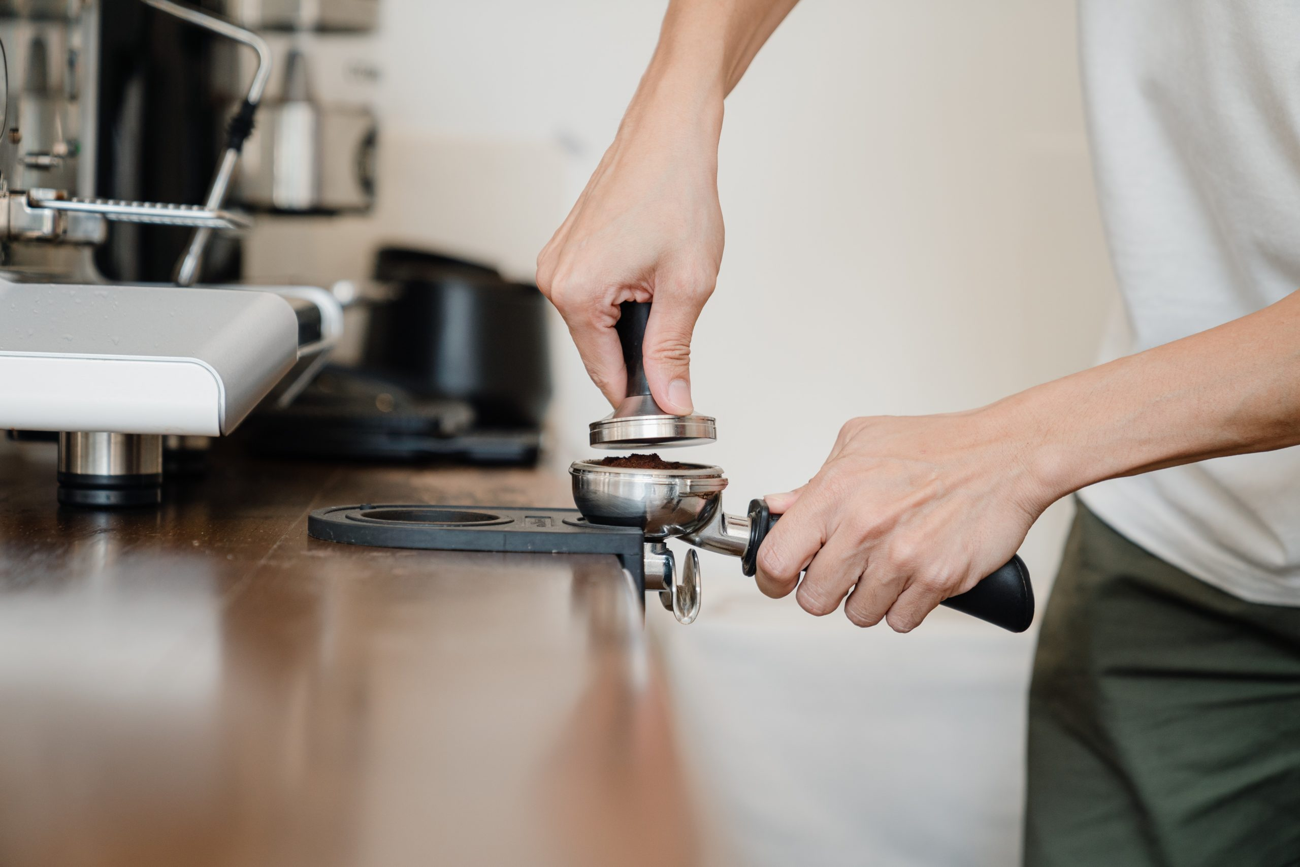a person tamping coffee