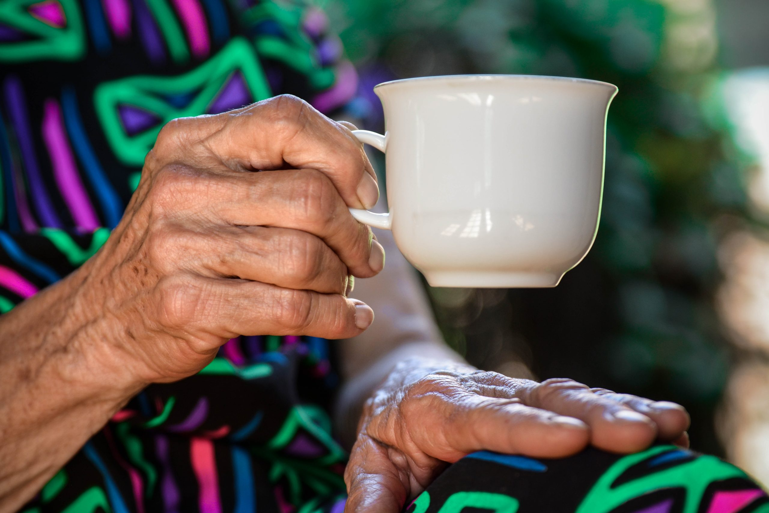 an old lady holding a cup