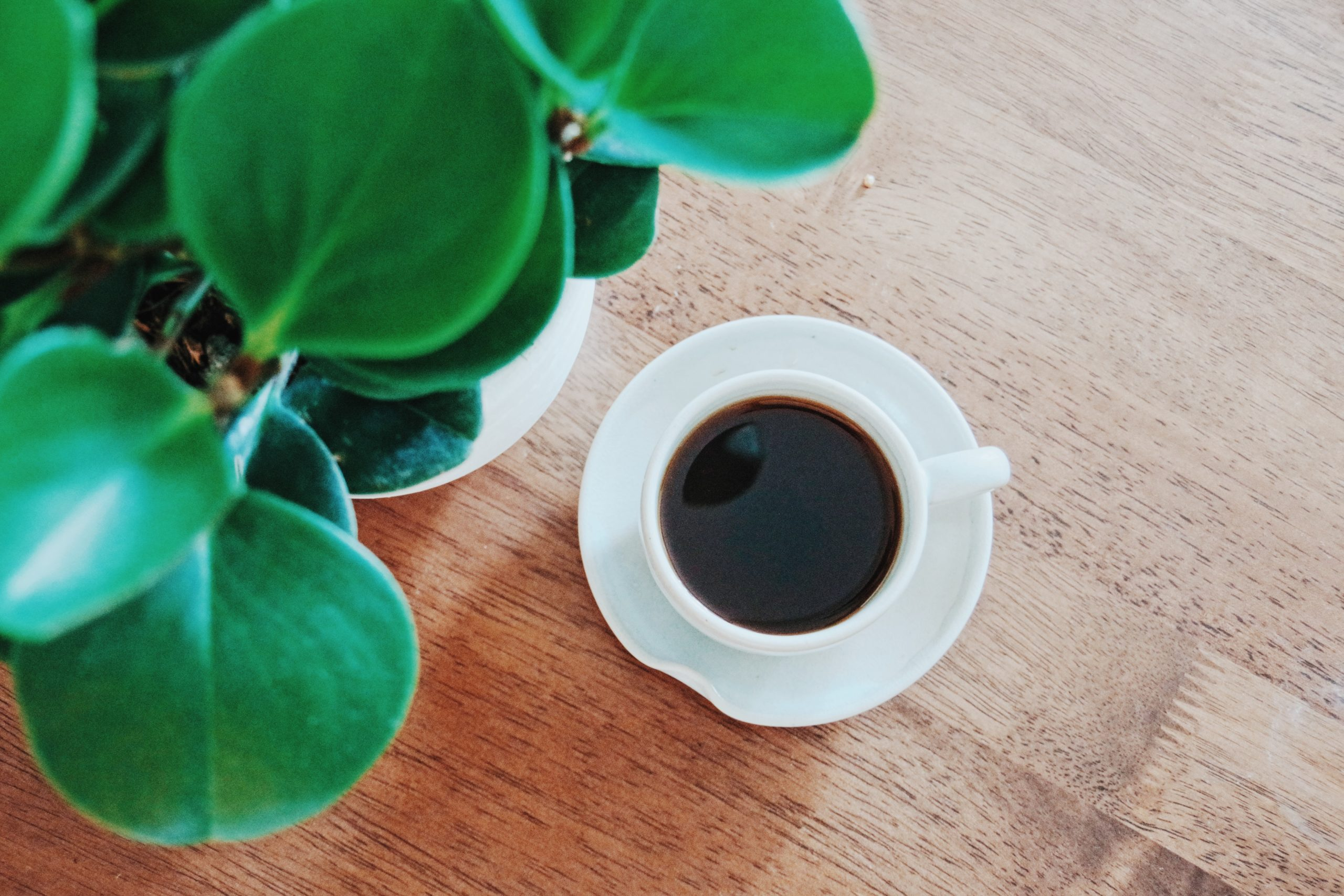 a cup of black coffee placed on a wooden table