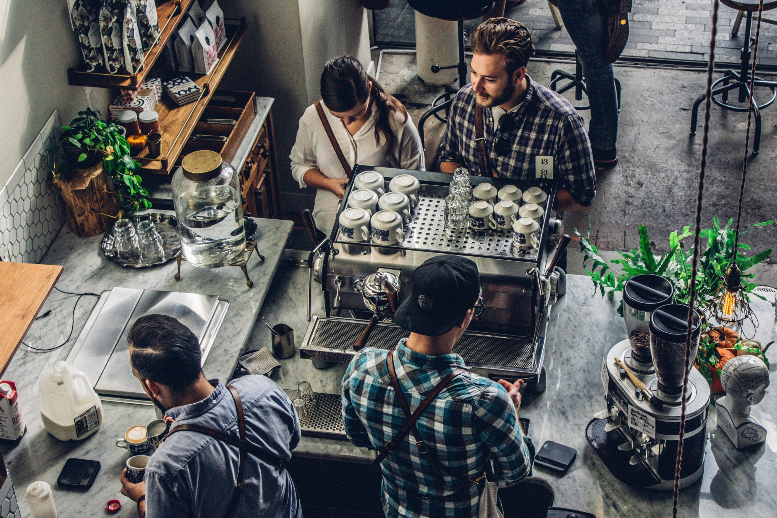 baristas serving coffee to customers over the counter