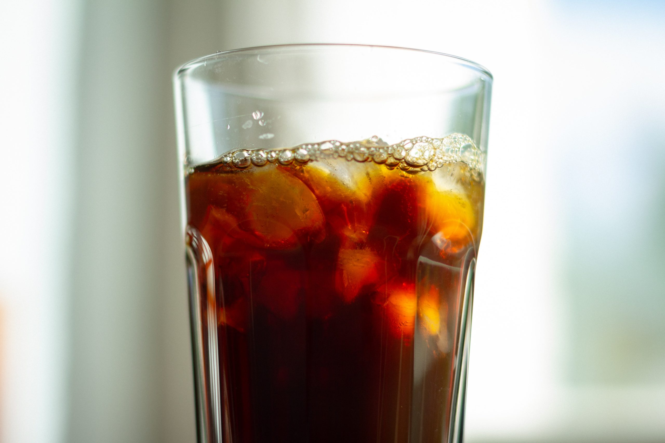 a glass of coffee with ice cubes