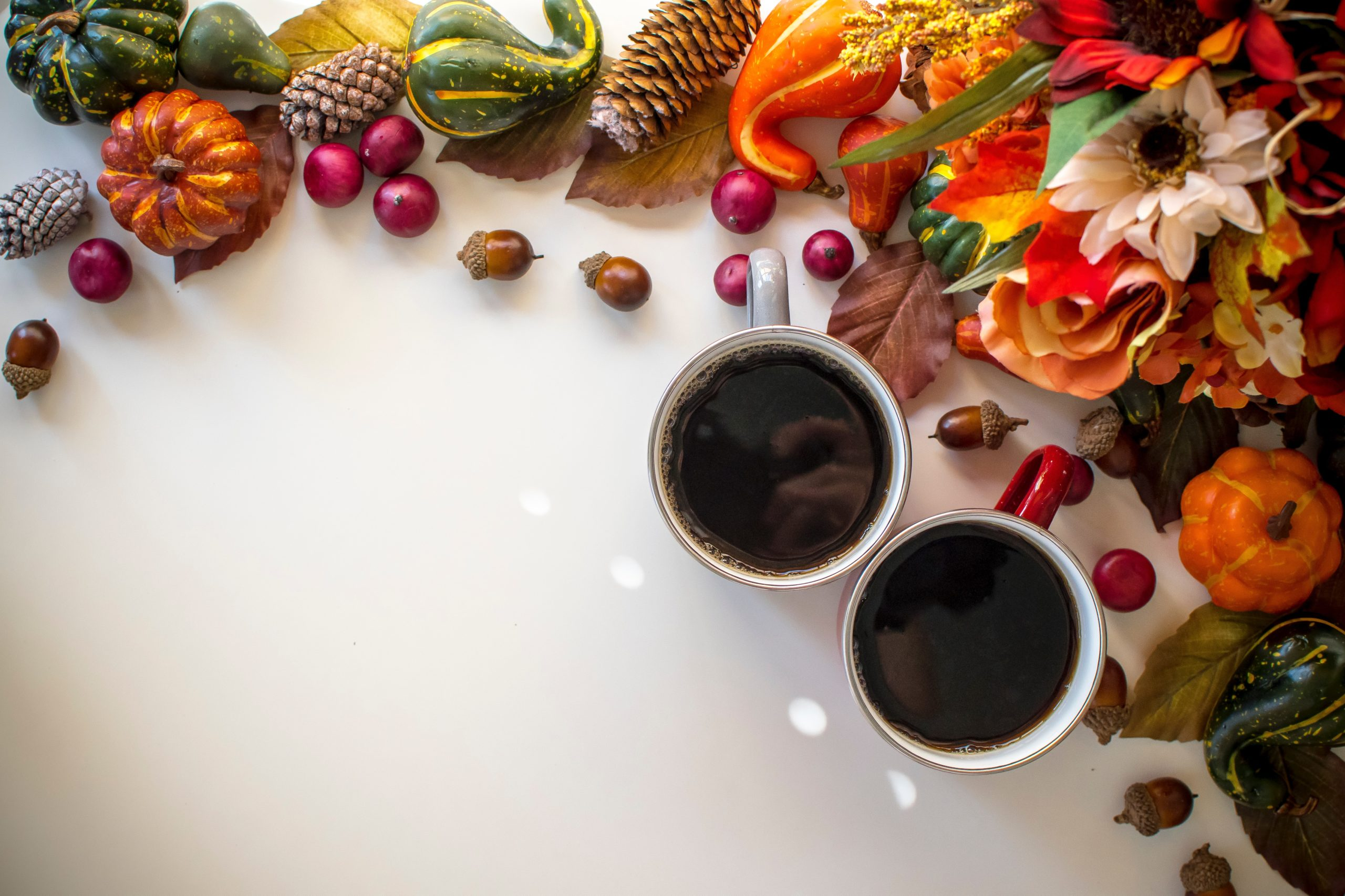 two cups of coffee surrounded by various fruits